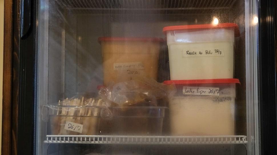 Des plats de sauce dans une réfrigérateur vitré.