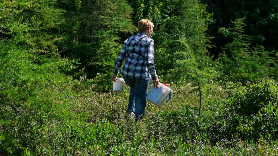 Une femme dans une tourbière avec des sacs et une chaudière à la main.