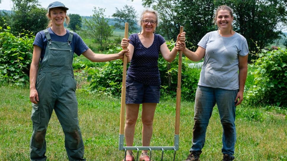 Trois femmes tenant une grelinette.