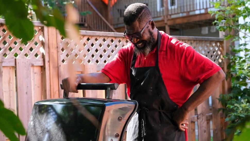 Un chef souriant en ouvrant un barbecue.