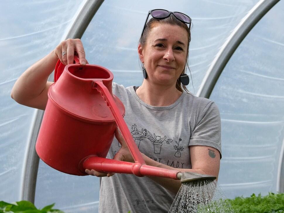 Une femme arrose des plantes et regarde la caméra.