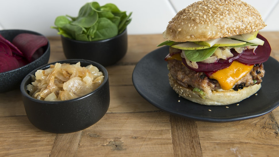 Un burger de porc avec bacon, oignons caramélisés et tranches de betteraves.