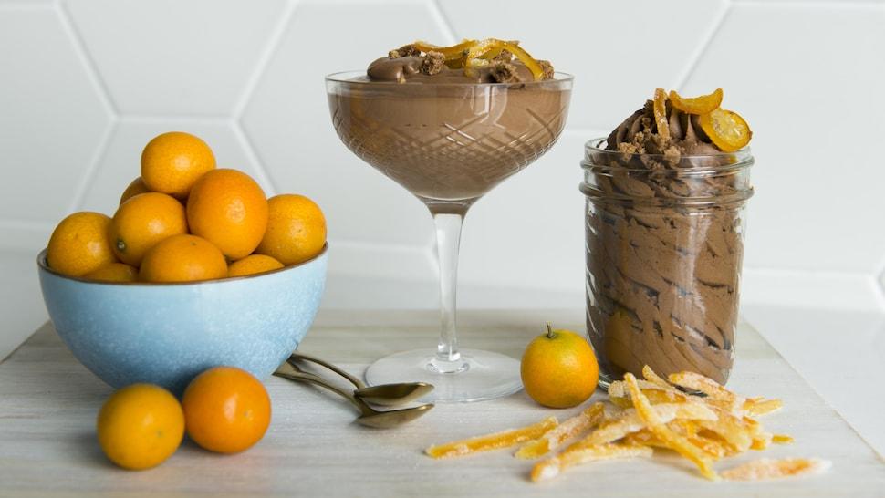 Une coupe et un pot en verre contiennent la mousse au chocolat.