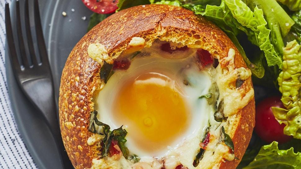 Œufs dans un bol de pain est accompagné d'une salada dans une assiette.