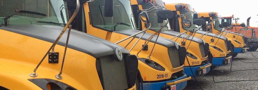 Une série d'autobus scolaires électriques branchés aux bornes de recharge.