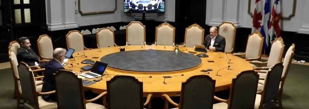 Le président du comité exécutif, Benoit Dorais, et deux représentants du greffe autour d'une grande table..