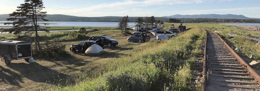 Des véhicules et des tentes sont installés entre une plage et un chemin de fer à Douglastown, en Gaspésie.