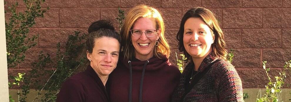 Trois femmes sont bras dessus, bras dessous devant un mur où apparaît le nom de l'école Nouvelle-frontière.