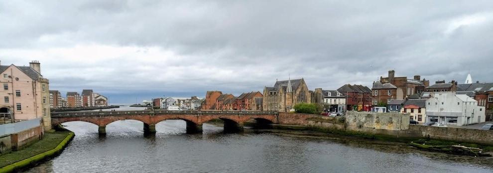 Une ville médiévale traversée par une rivière et un pont.