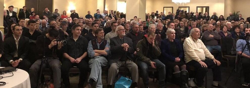 Les partisans sont assis dans une vaste salle de l'hôtel Atlantica.