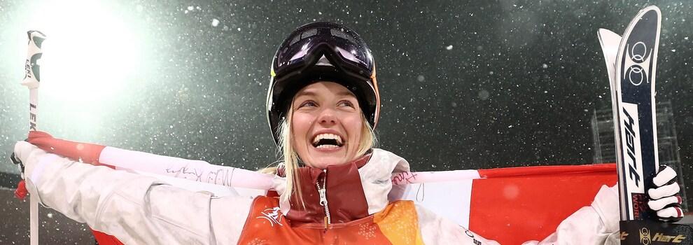 La skieuse acrobatique Justine Dufour-Lapointe sourit en brandissant le drapeau du Canada.