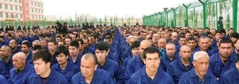On voit plusieurs prisonniers Ouïgours assis en rang dans un camp d'internement.