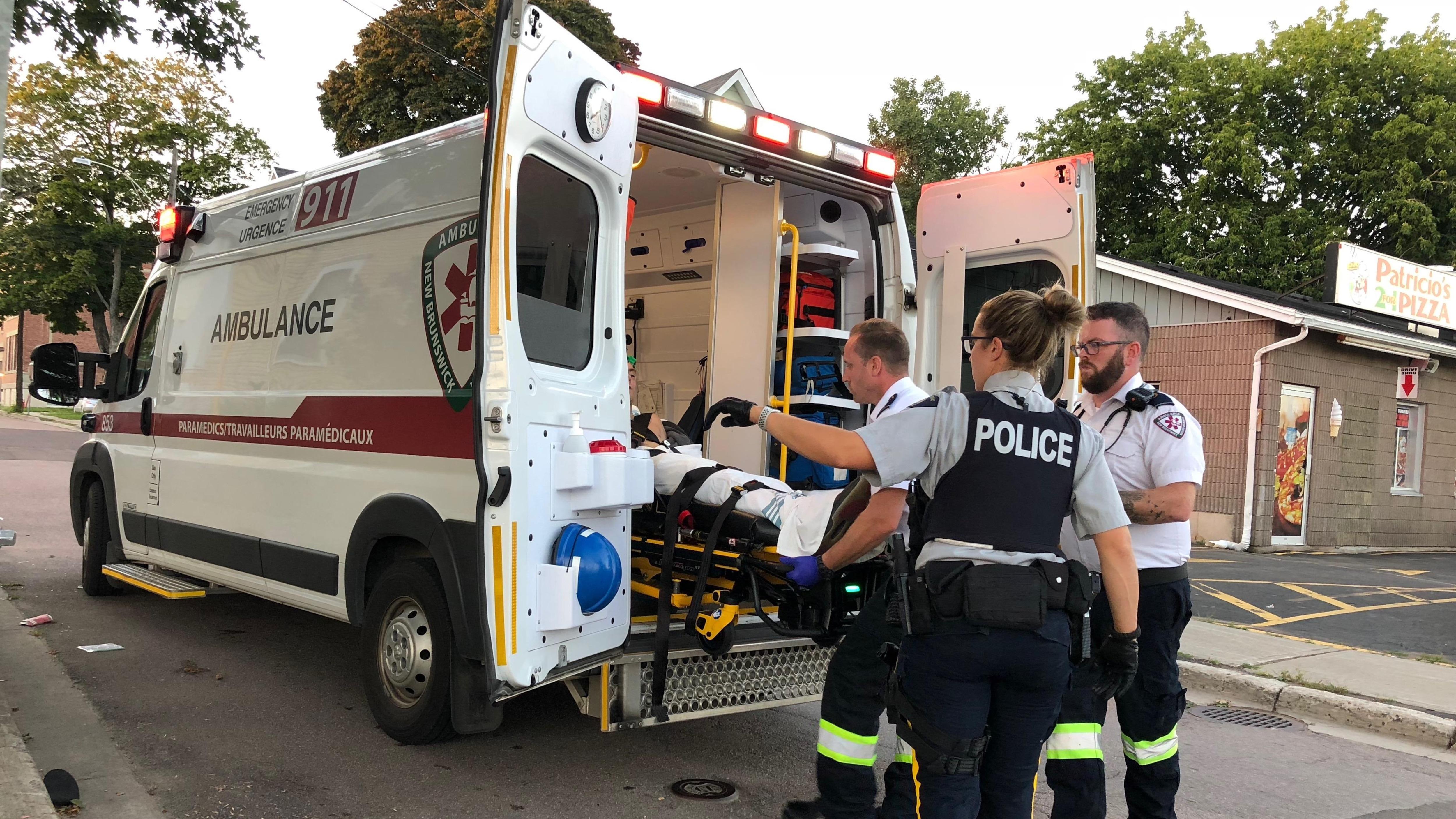 Deux ambulanciers et une policière traitent un individu transporté dans le camion sur une civière.