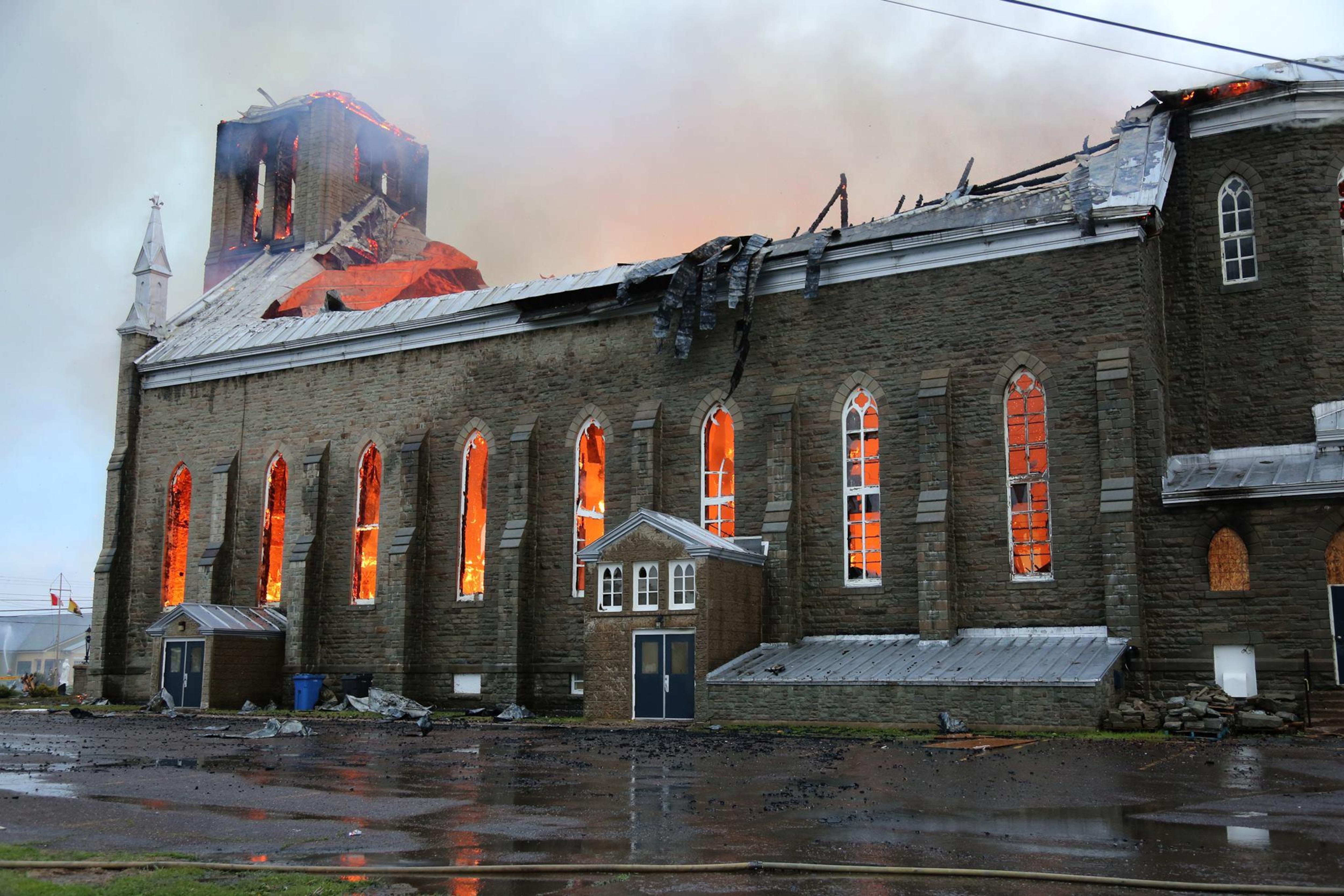 La lueur des flammes éclaire l'intérieur de l'église en ruines