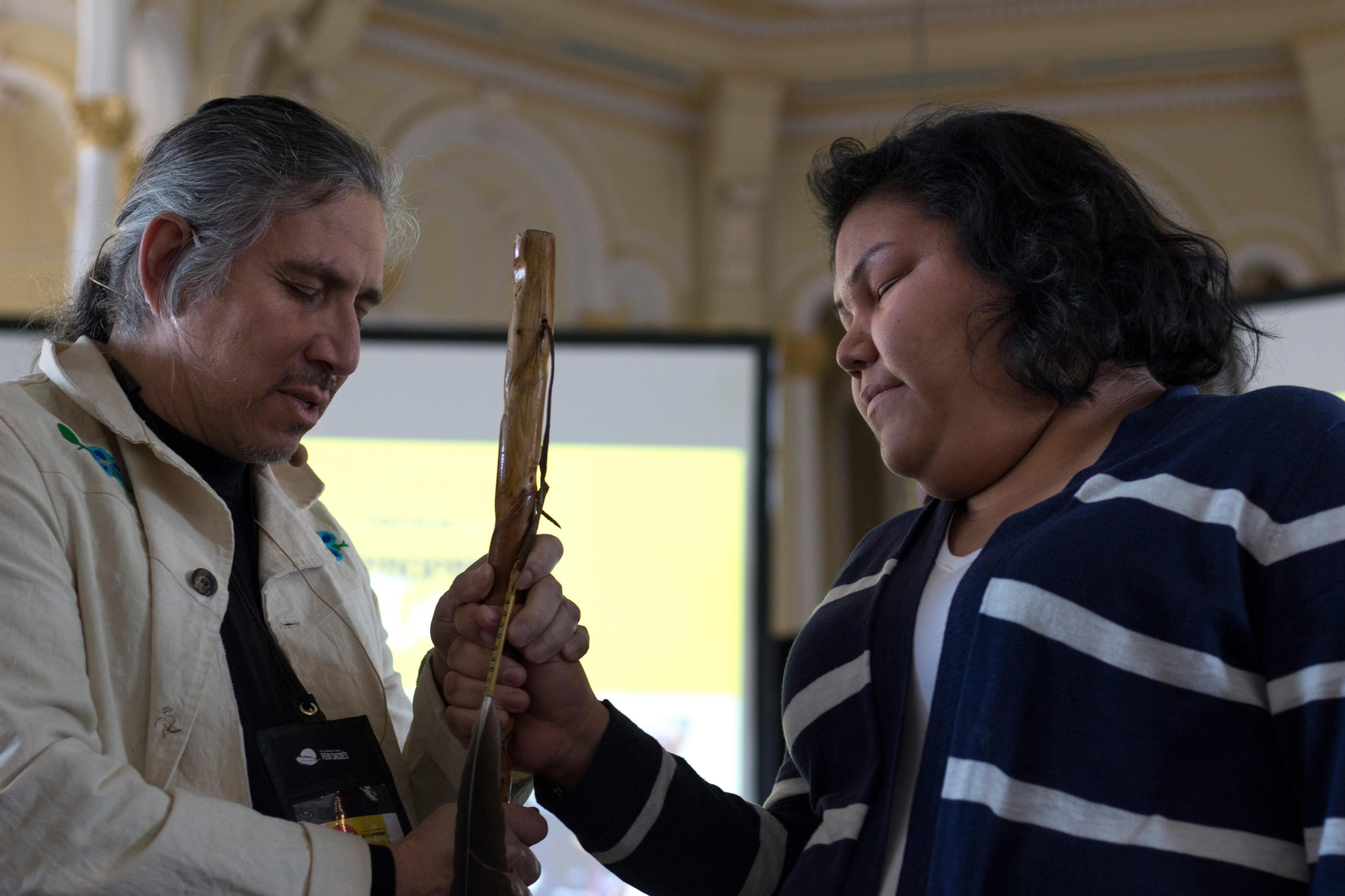 Le docteur et une jeune Innue tiennent dans leurs mains un bâton de marche.