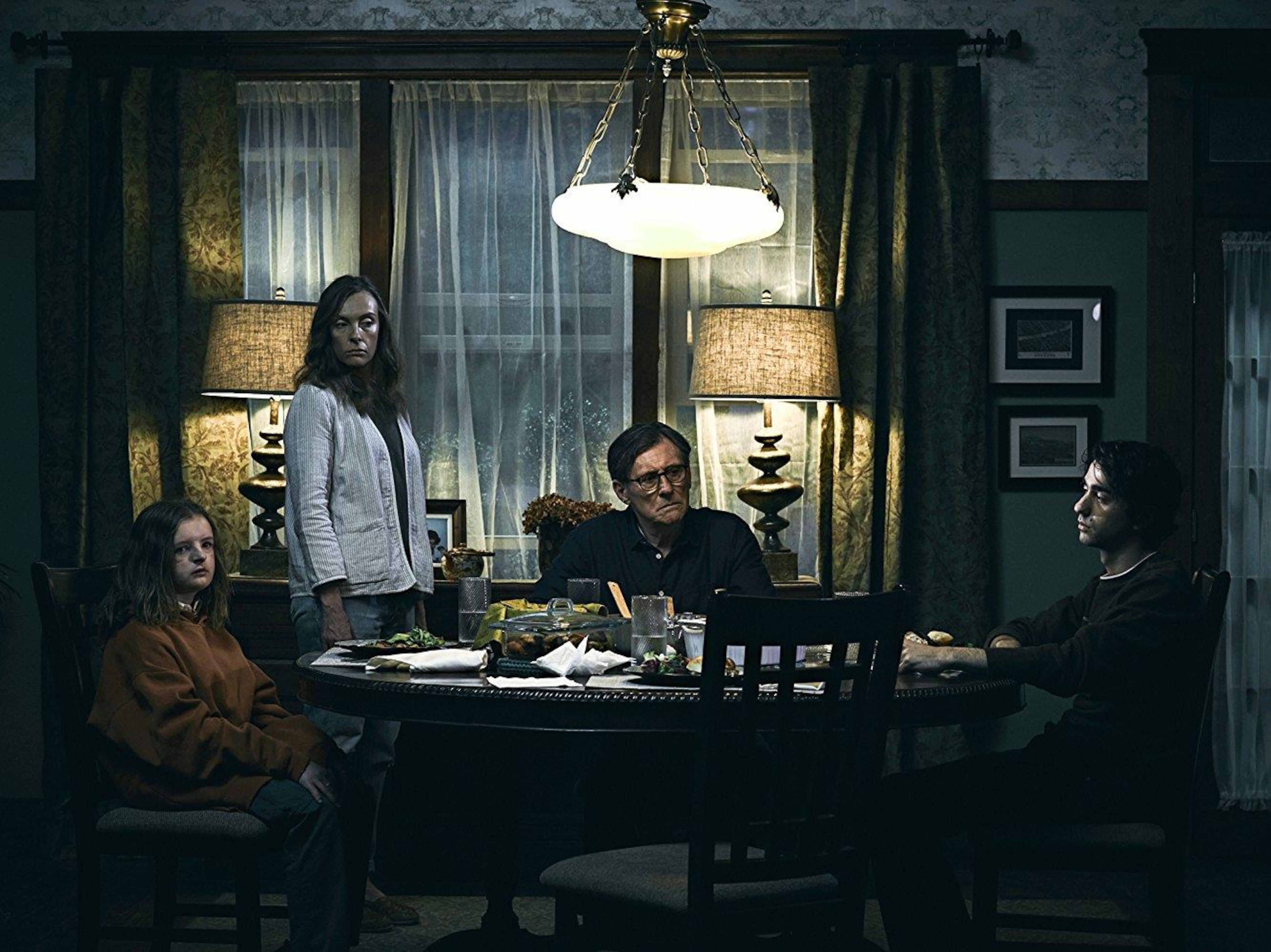 Deux enfants et un homme sont assis à une table ronde pendant qu'une femme se tient debout.