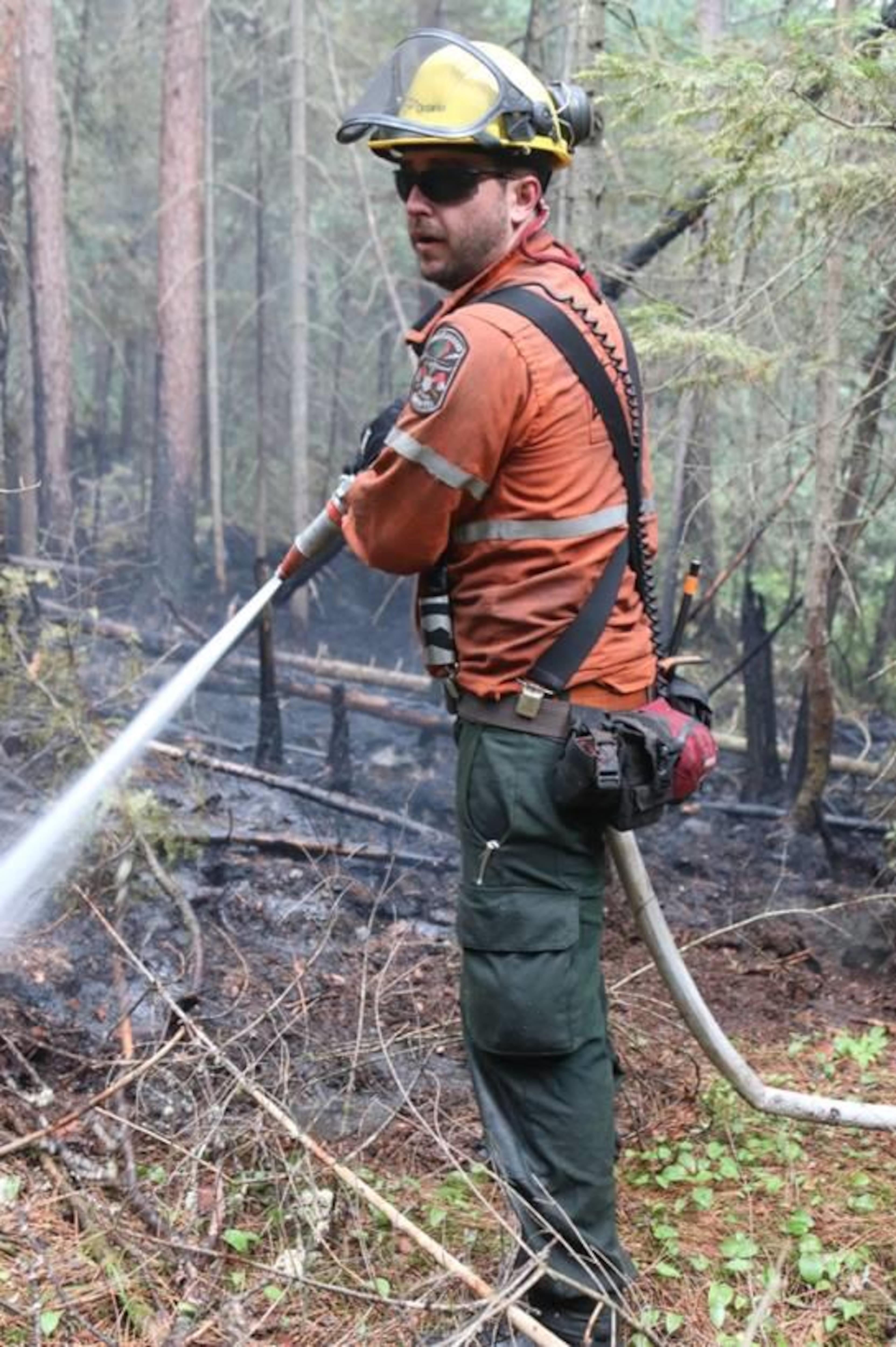 Un pompier qui arrose le sol en forêt.