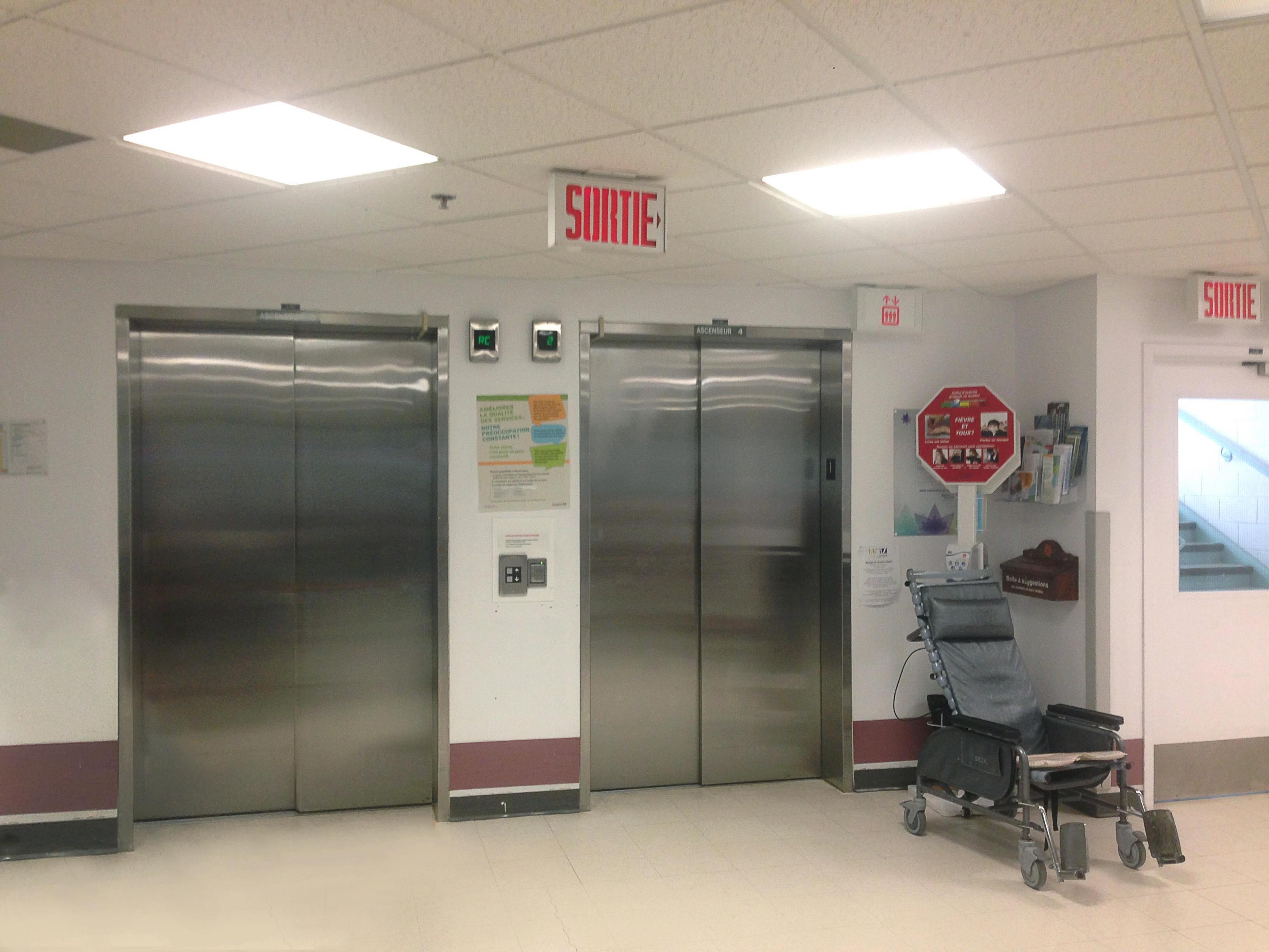 Des portes d'ascenseurs d'un CHSLD. Un fauteuil roulant se trouve à proximité.
