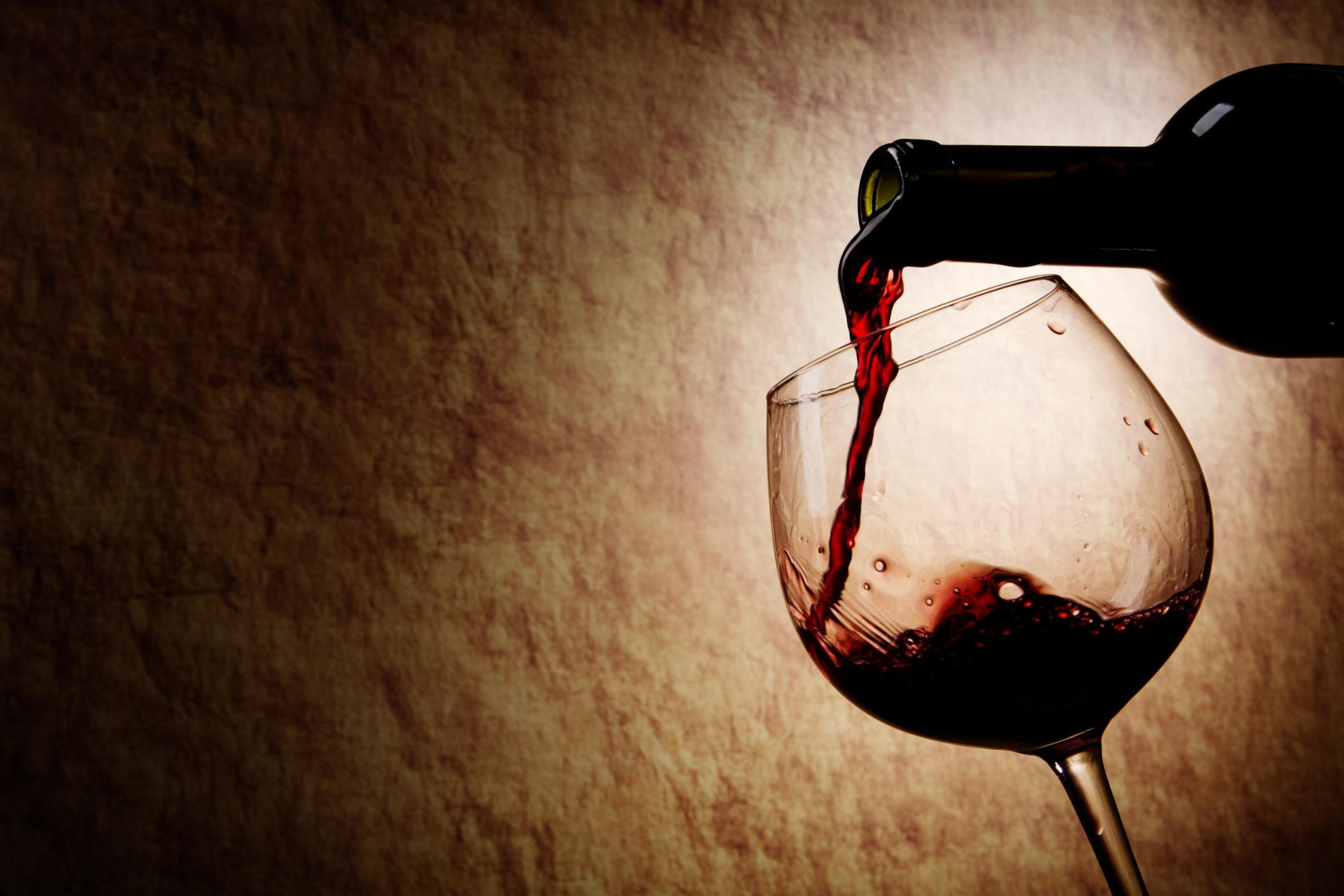 Du vin rouge est versé dans un verre à vin.