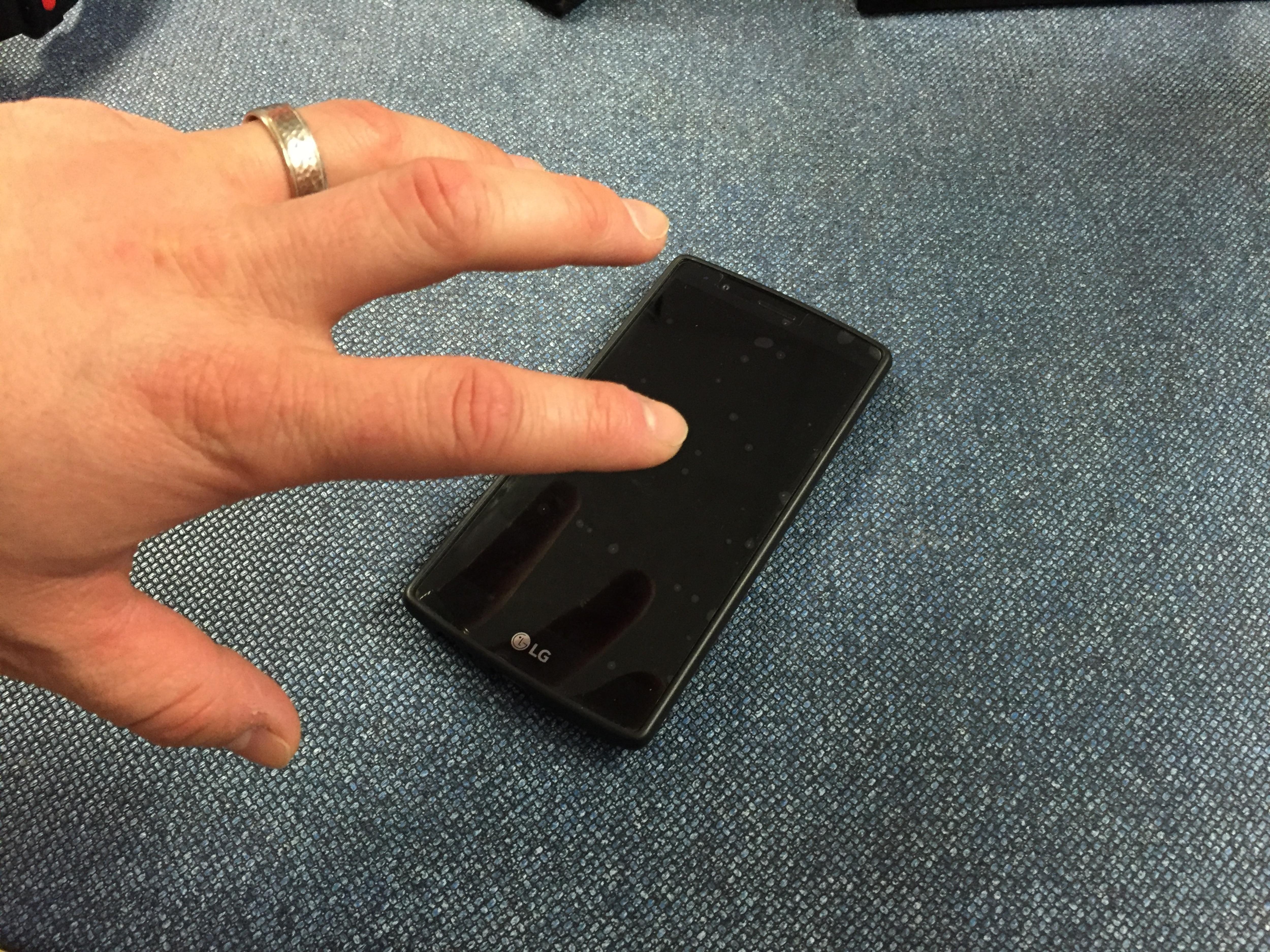 Une main qui prend un cellulaire.