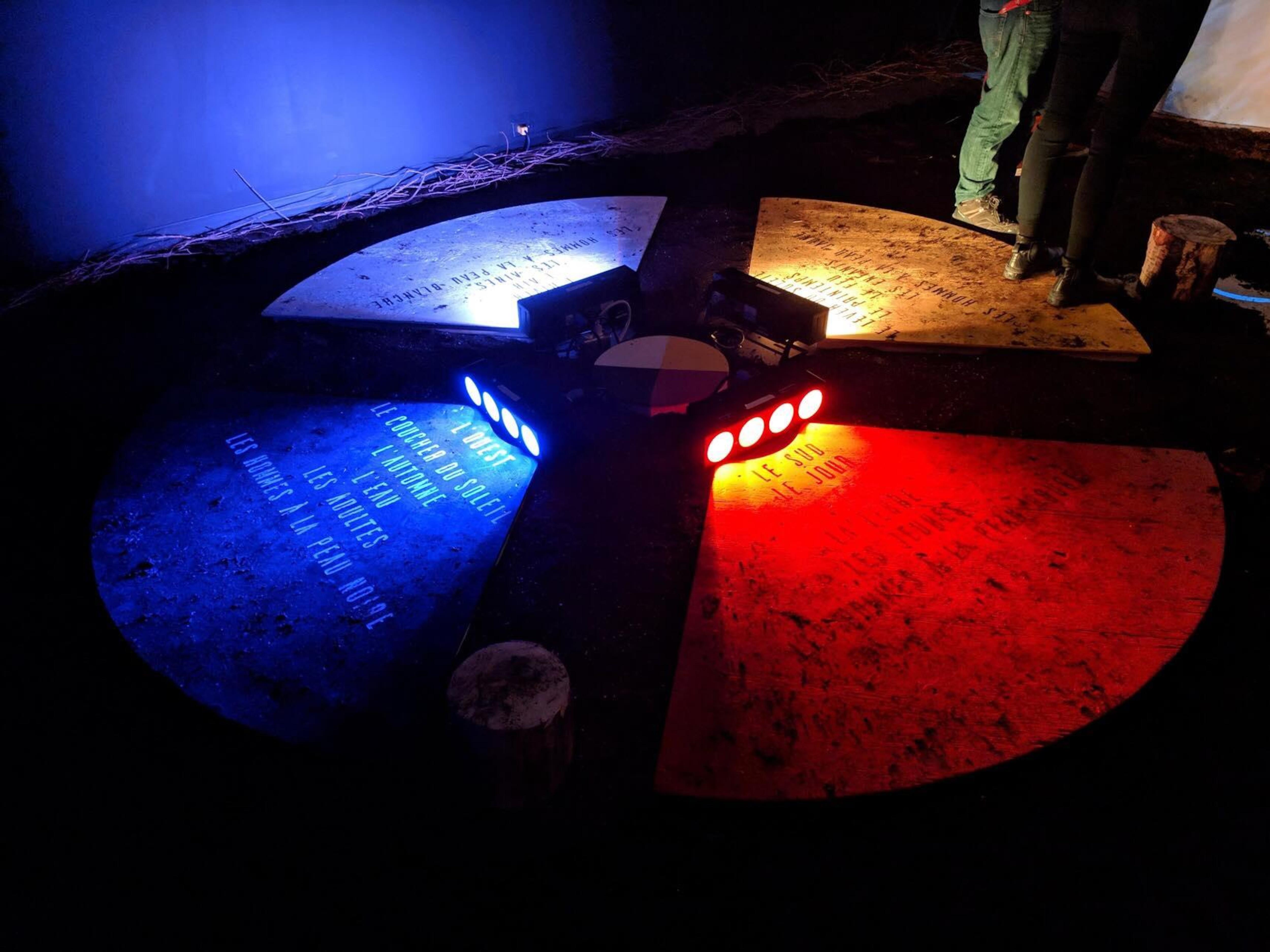 Des lumières de couleurs différentes illuminent le sol où il est inscrit des informations sur l'histoire des autochtones de la région.