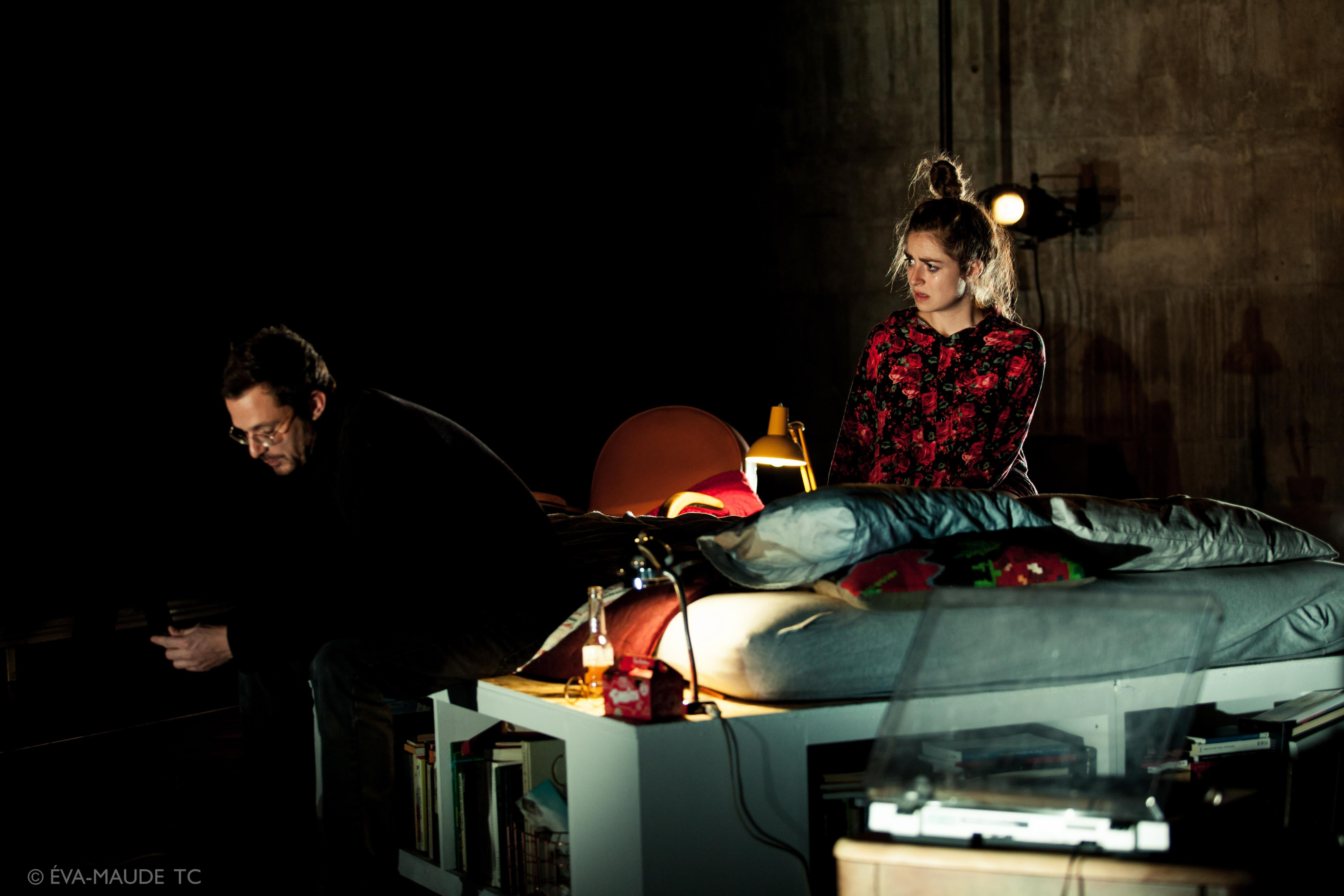 Un homme est assis au bout d'un lit, il regarde son téléphone dans ses mains, alors qu'une femme à genoux sur le lit le regarde.