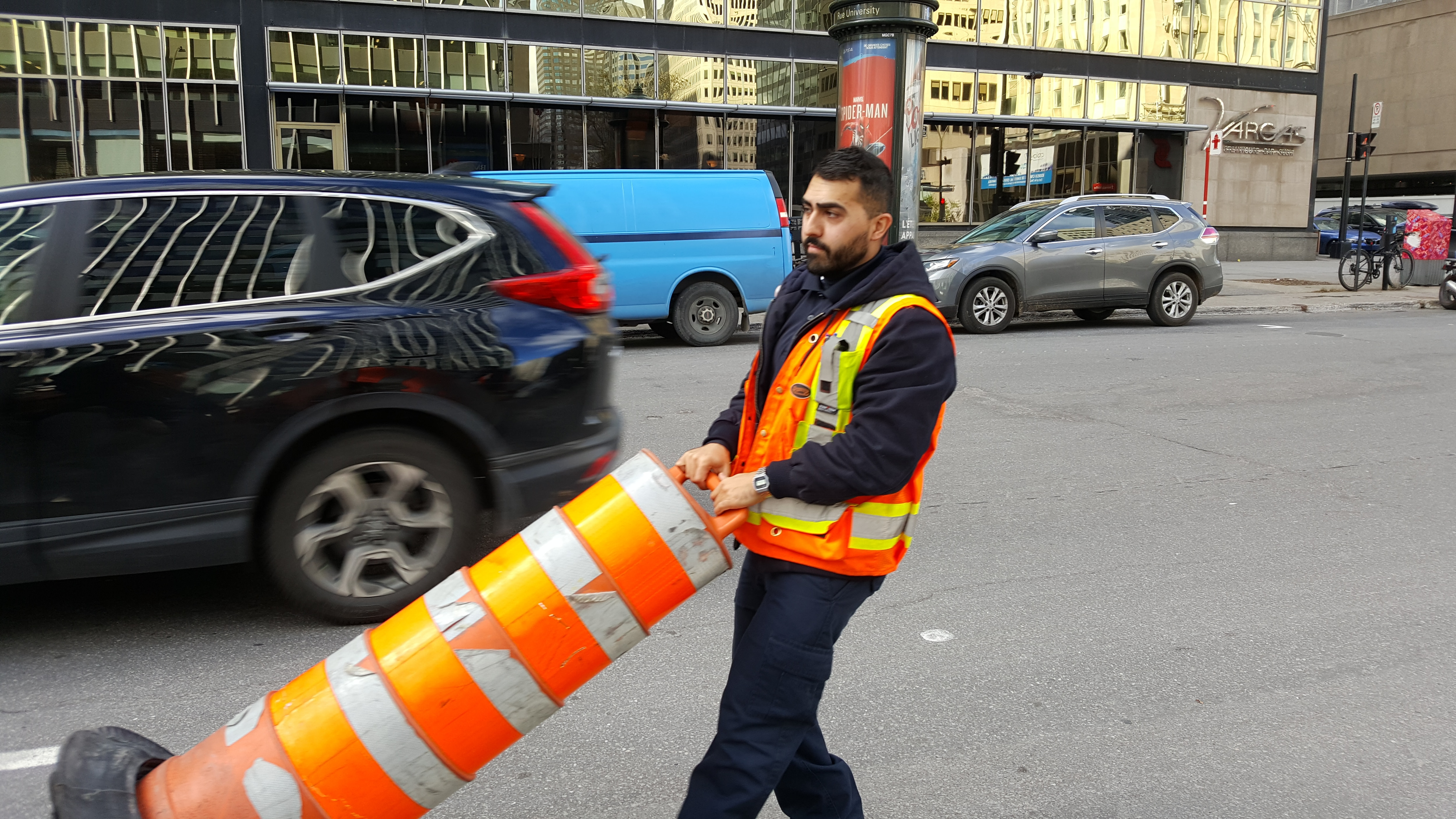 Un homme portant un dossard orange tire un cône dans une rue.
