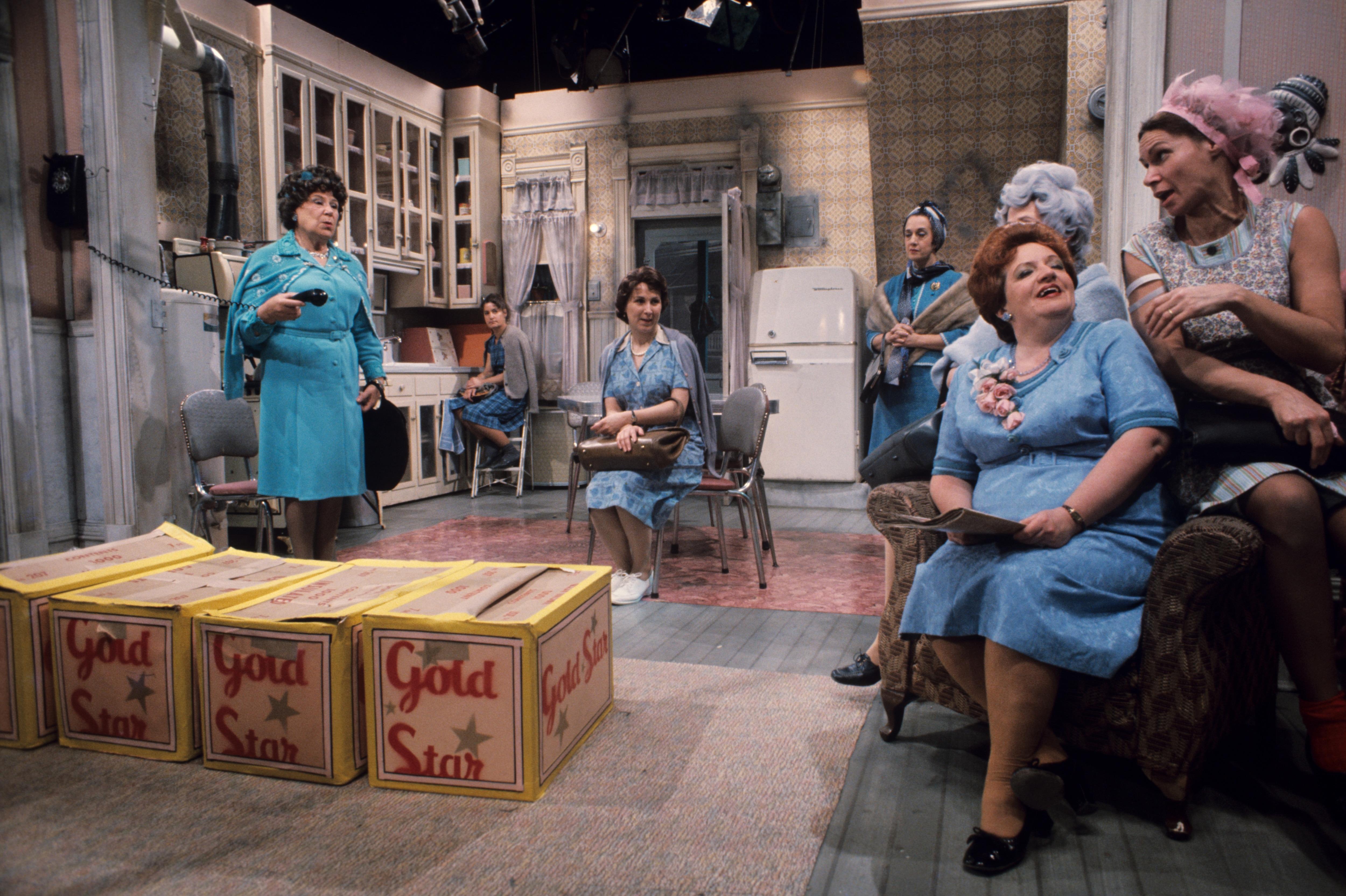 Dans une cuisine,  Yvette Longpré (Sylvie Heppel), avec le récepteur du téléphone à la main, Marie-Ange Brouillette (Amulette Garneau), Desneiges Verrette (Rita Lafontaine), Lisette de Courval, (Denise Morelle), Gabrielle Jodoin (Eve Gagnier), Germaine Lauzon (Denise Proulx) et Rose Ouimet (Monique Mercure).