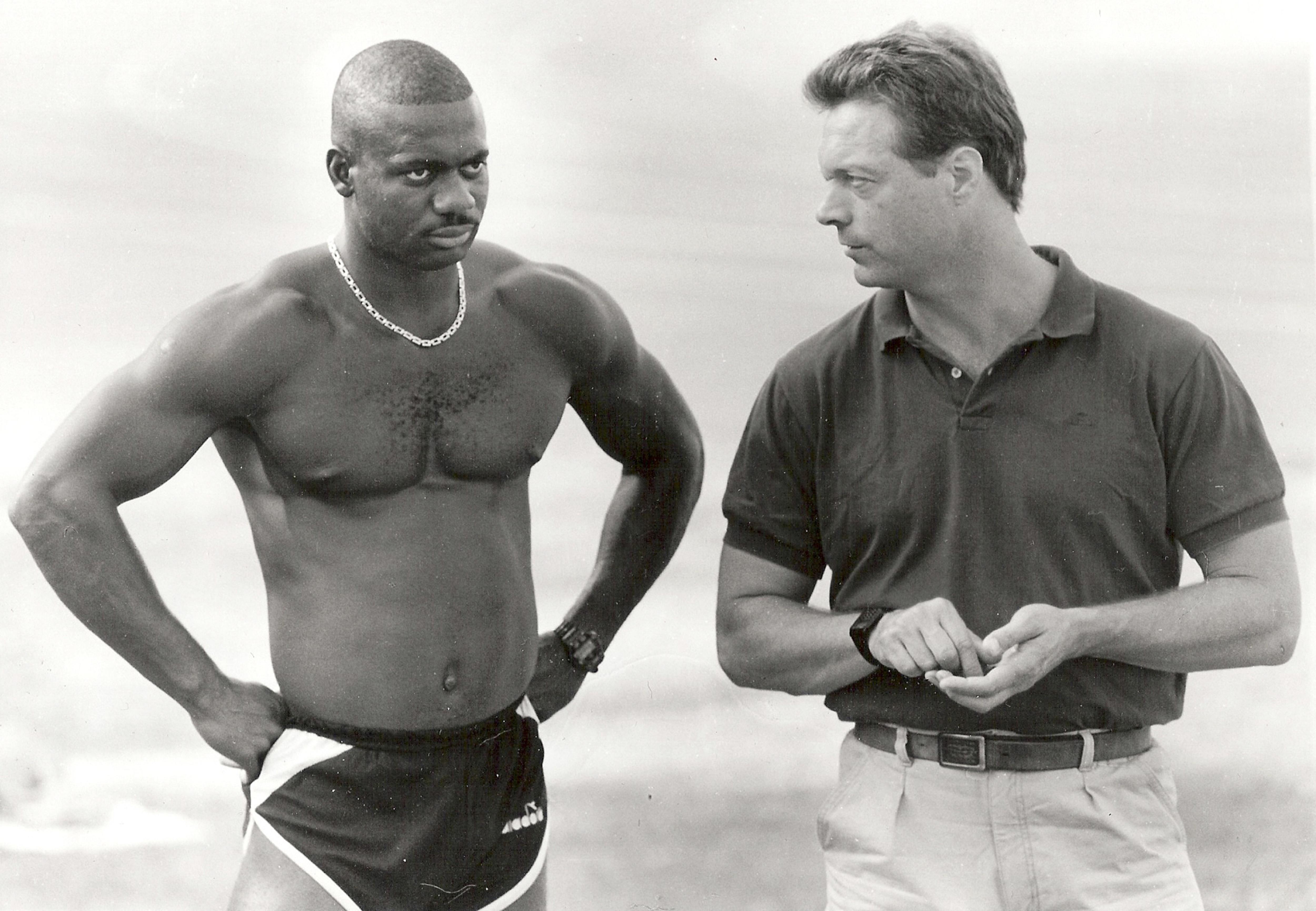 Ben Johnson torse nu est regardé par son entraîneur Charlie Francis.