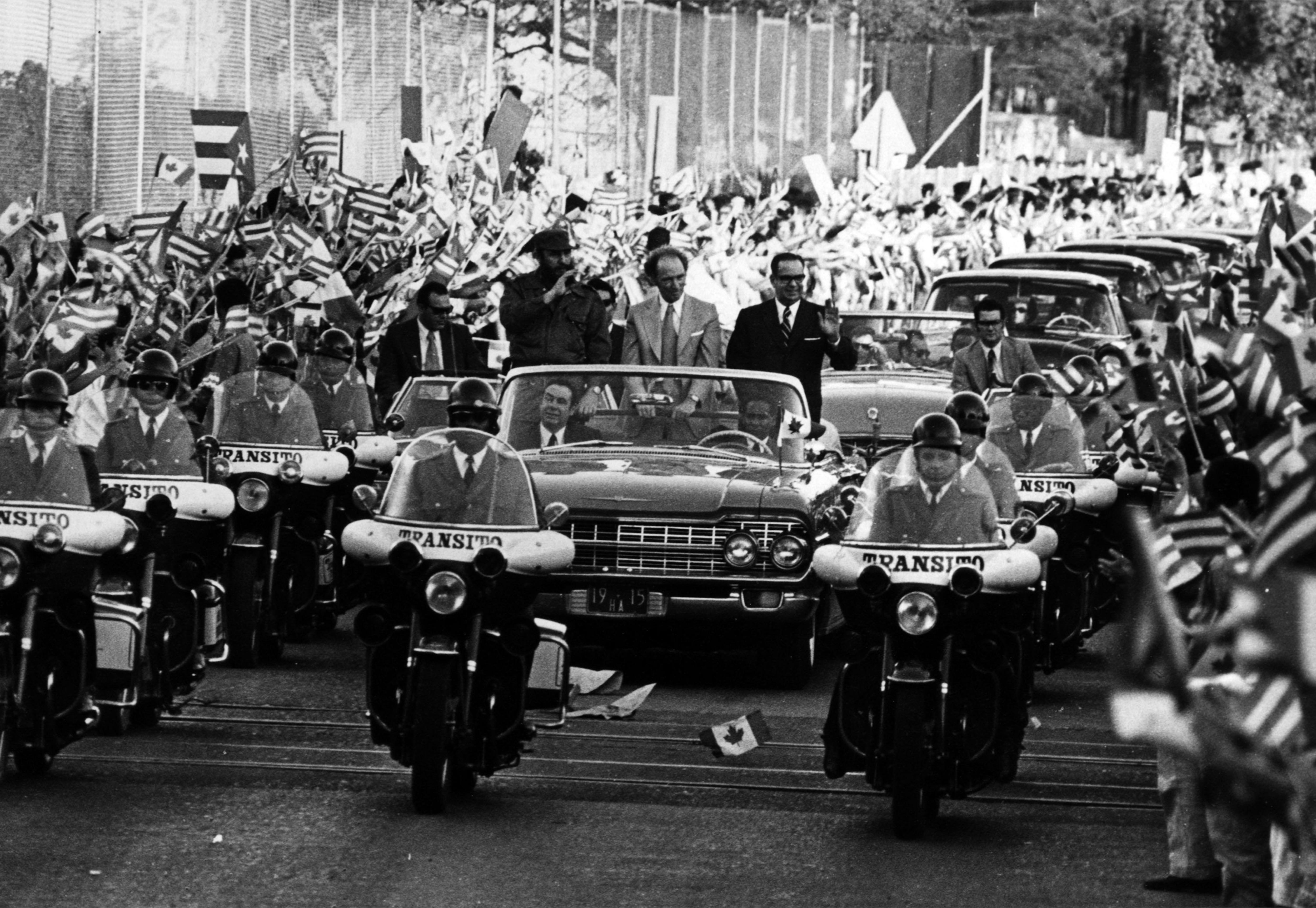 Castro et Trudeau paradent debout dans une voiture officielle décapotable.