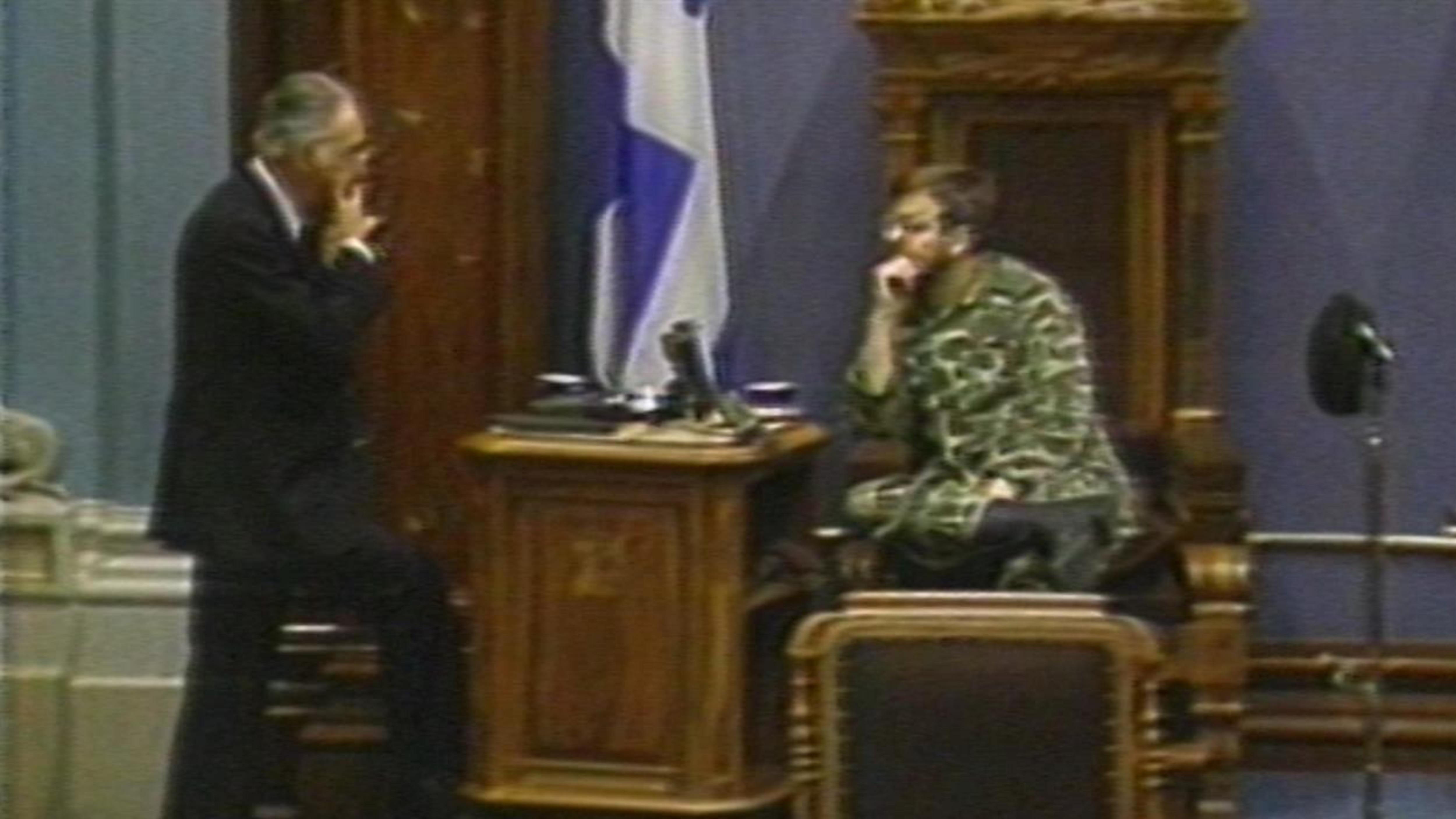 À l'Assemblée nationale du Québec, un homme discute avec un militaire qui est assis sur un trône.