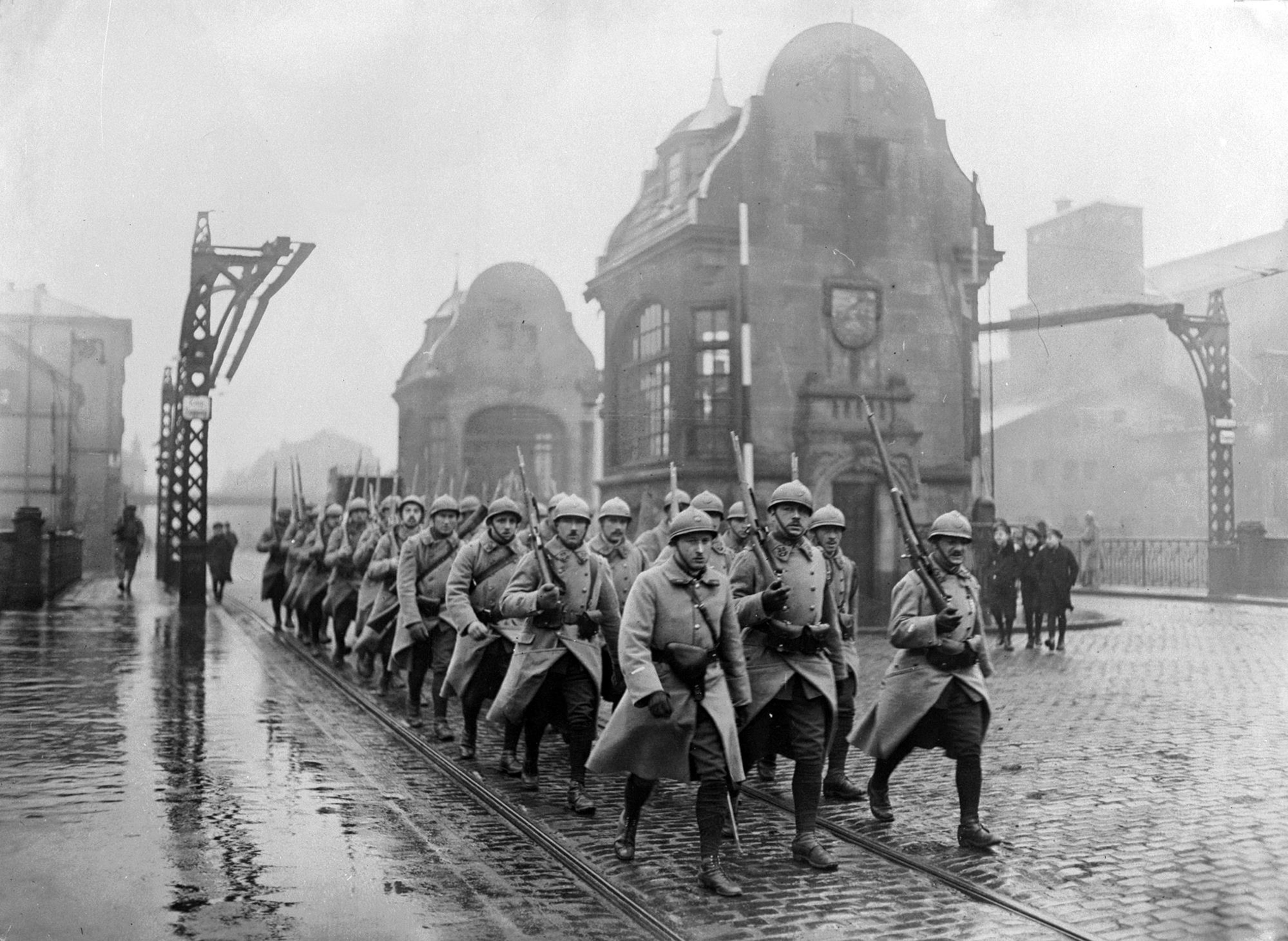 Photo en noir et blanc d'un groupe de soldats marchant dans une rue.