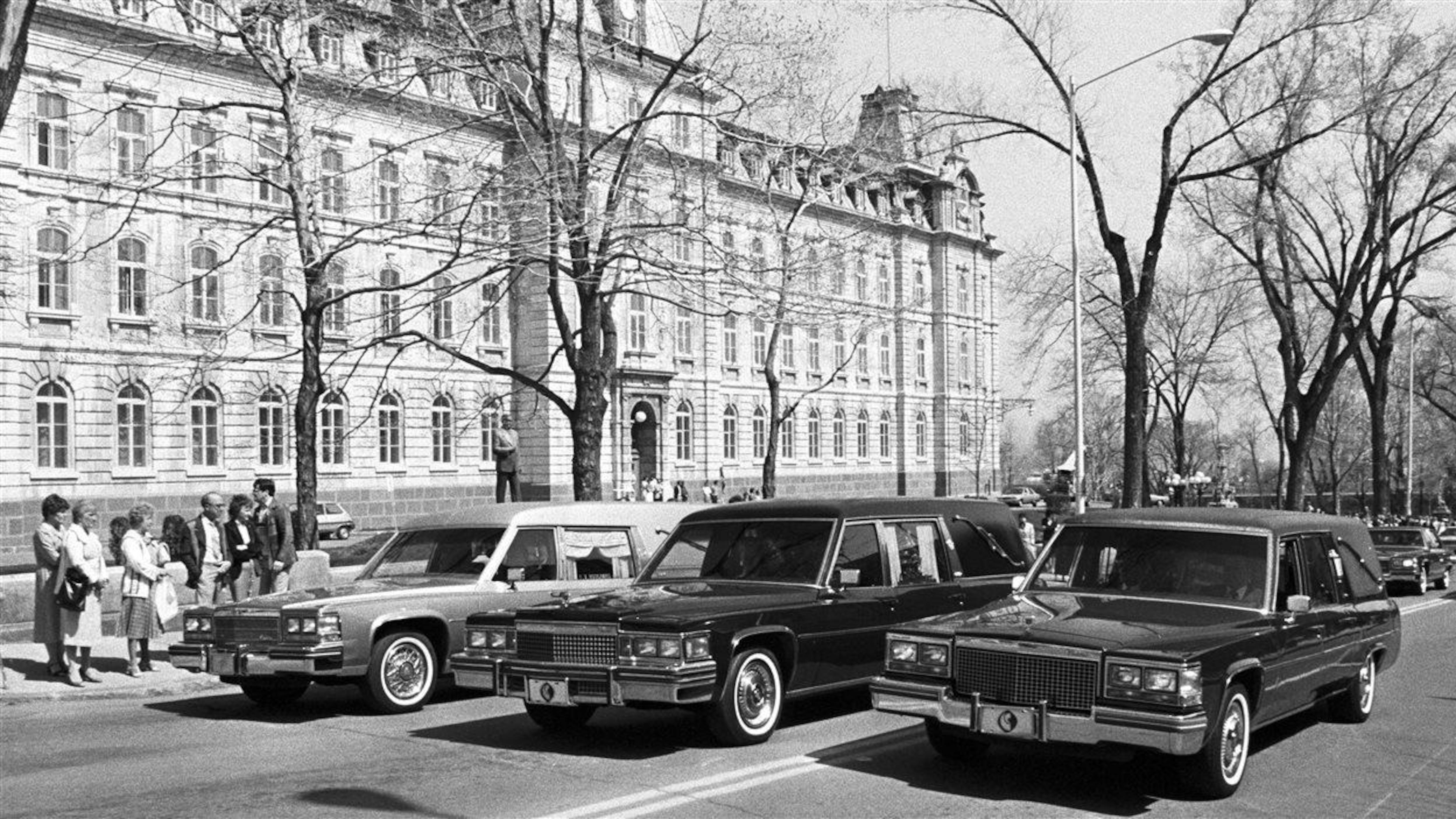 Photo en noir et blanc de trois corbillards circulant sur une rue alors que des piétons les regardent.