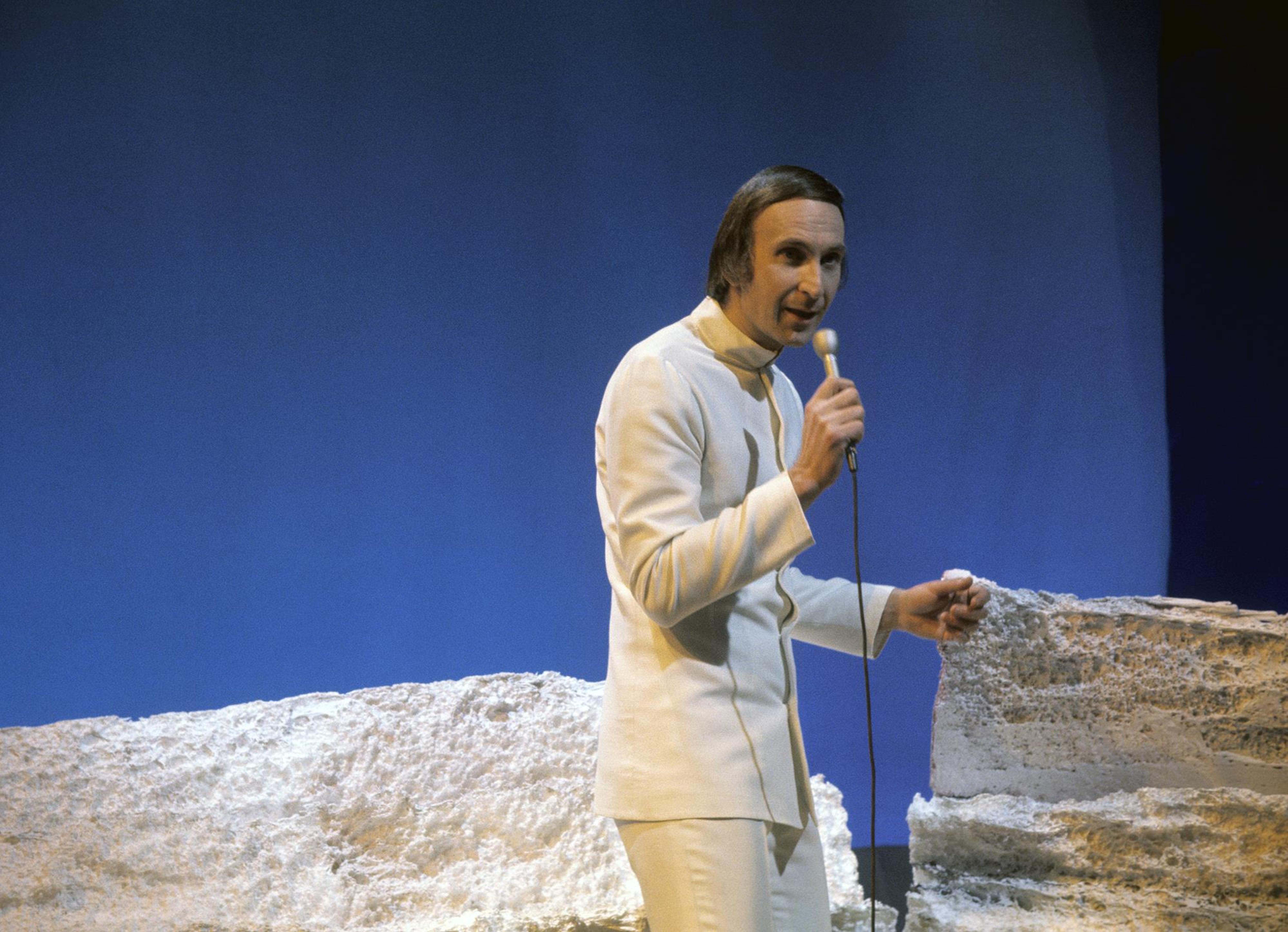 Un homme tient un micro; deux pierres se trouvent derrière lui.
