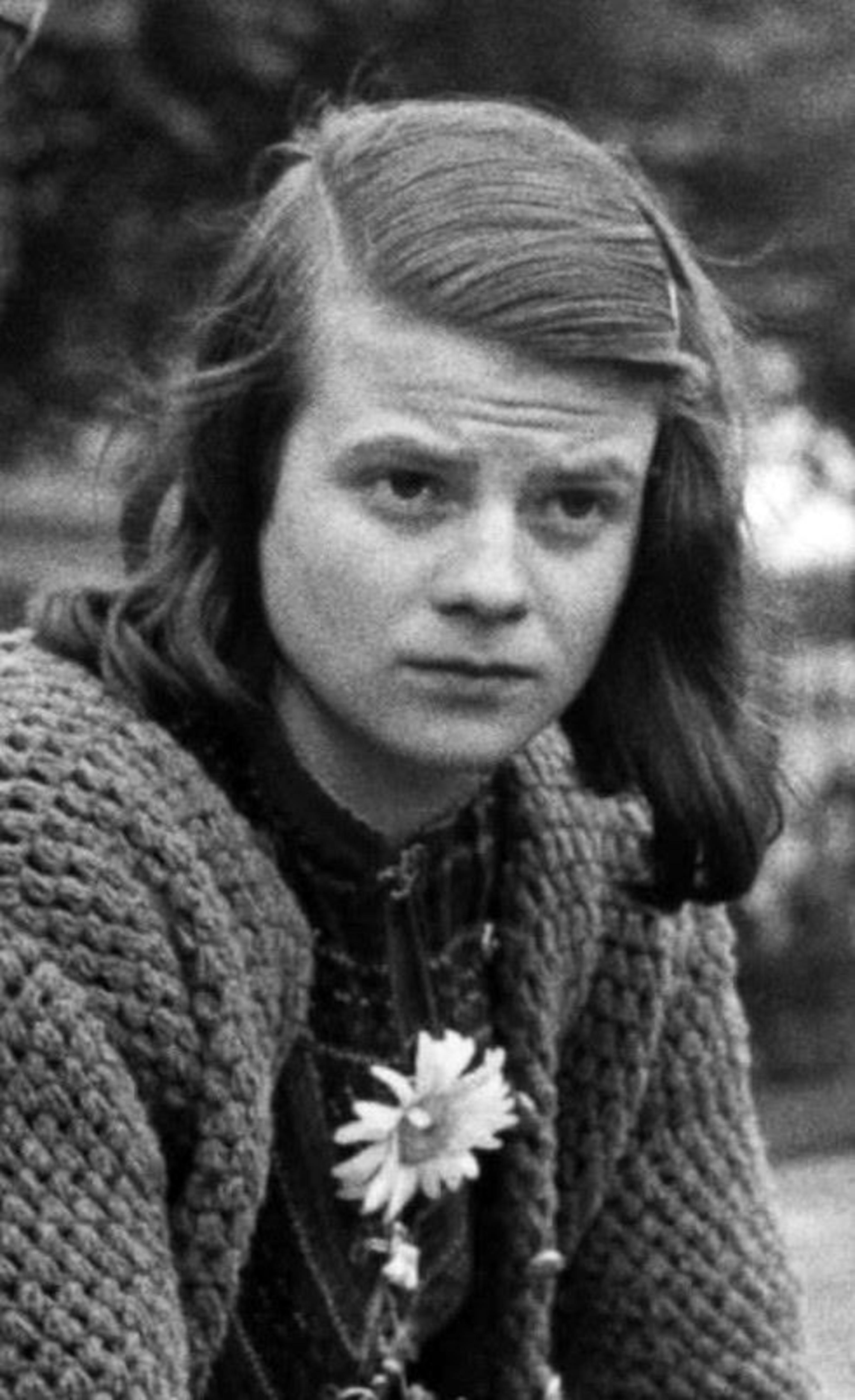 Photo en noir et blanc d'une jeune femme portant une fleur sur son vêtement.