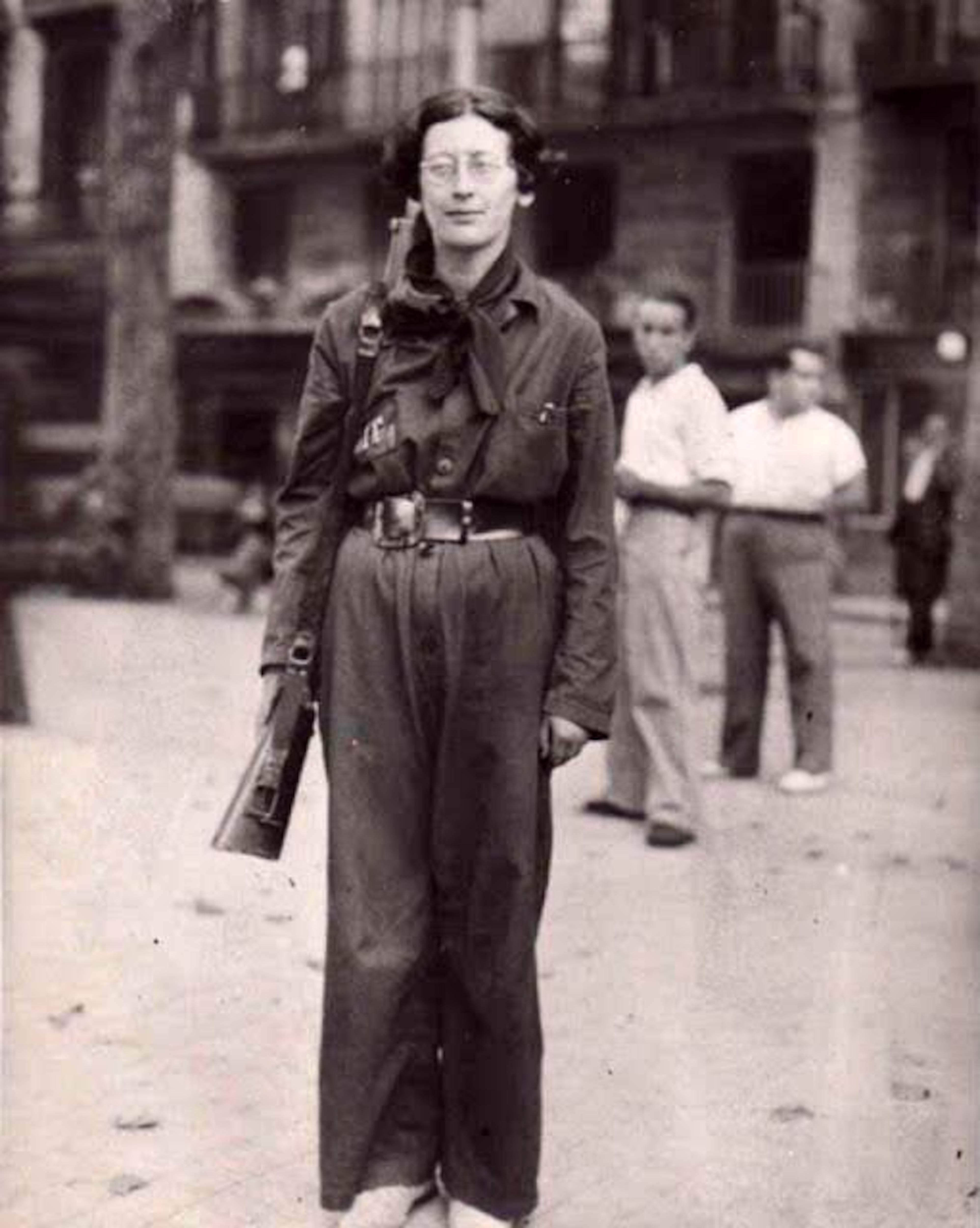 Une femme est debout avec une arme en bandoulière. Deux hommes sont en arrière champ.