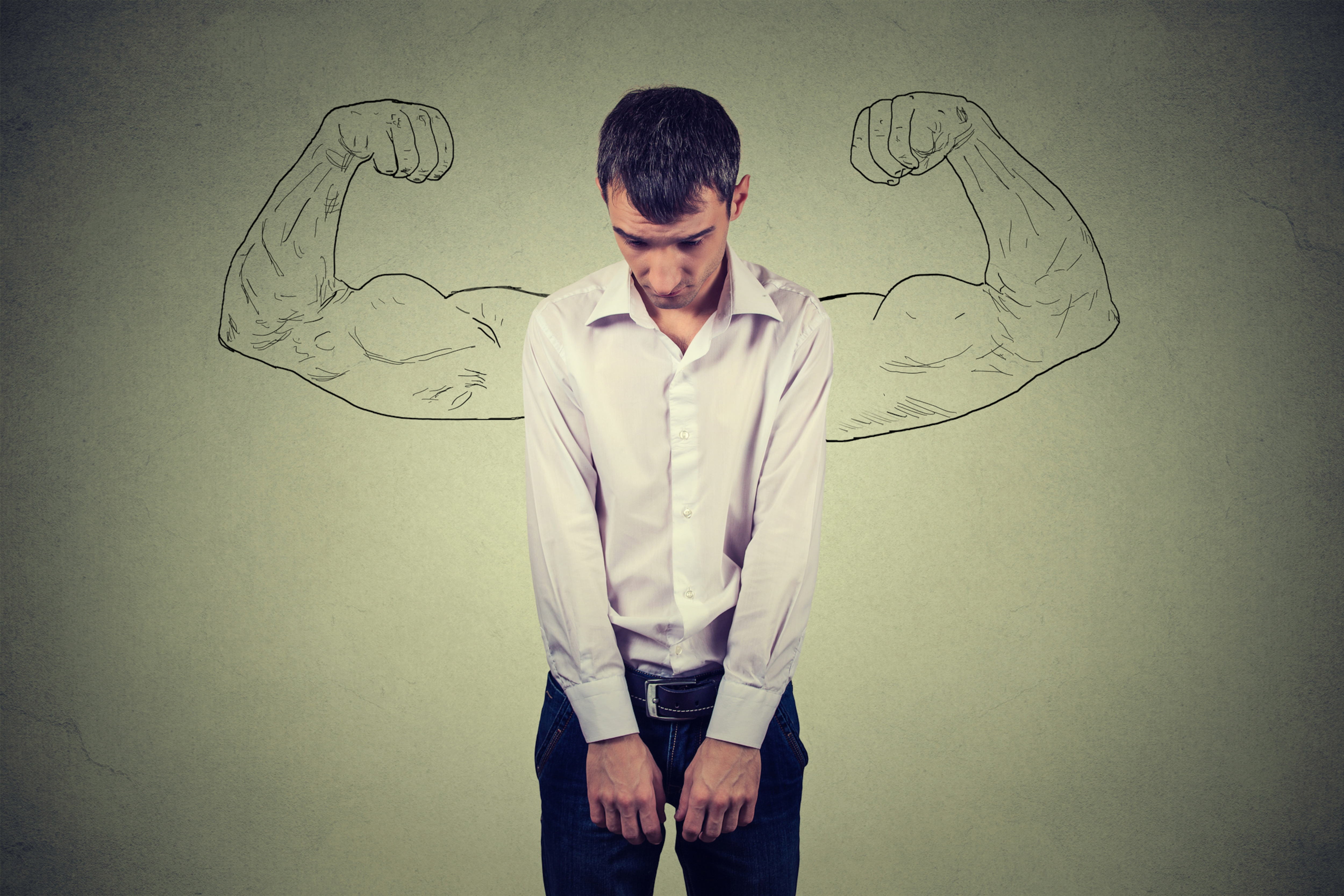 Une jeune homme mince et déprimé, la tête baissée, aimerait avoir des muscles comme ceux dessinés sur un mur derrière lui.