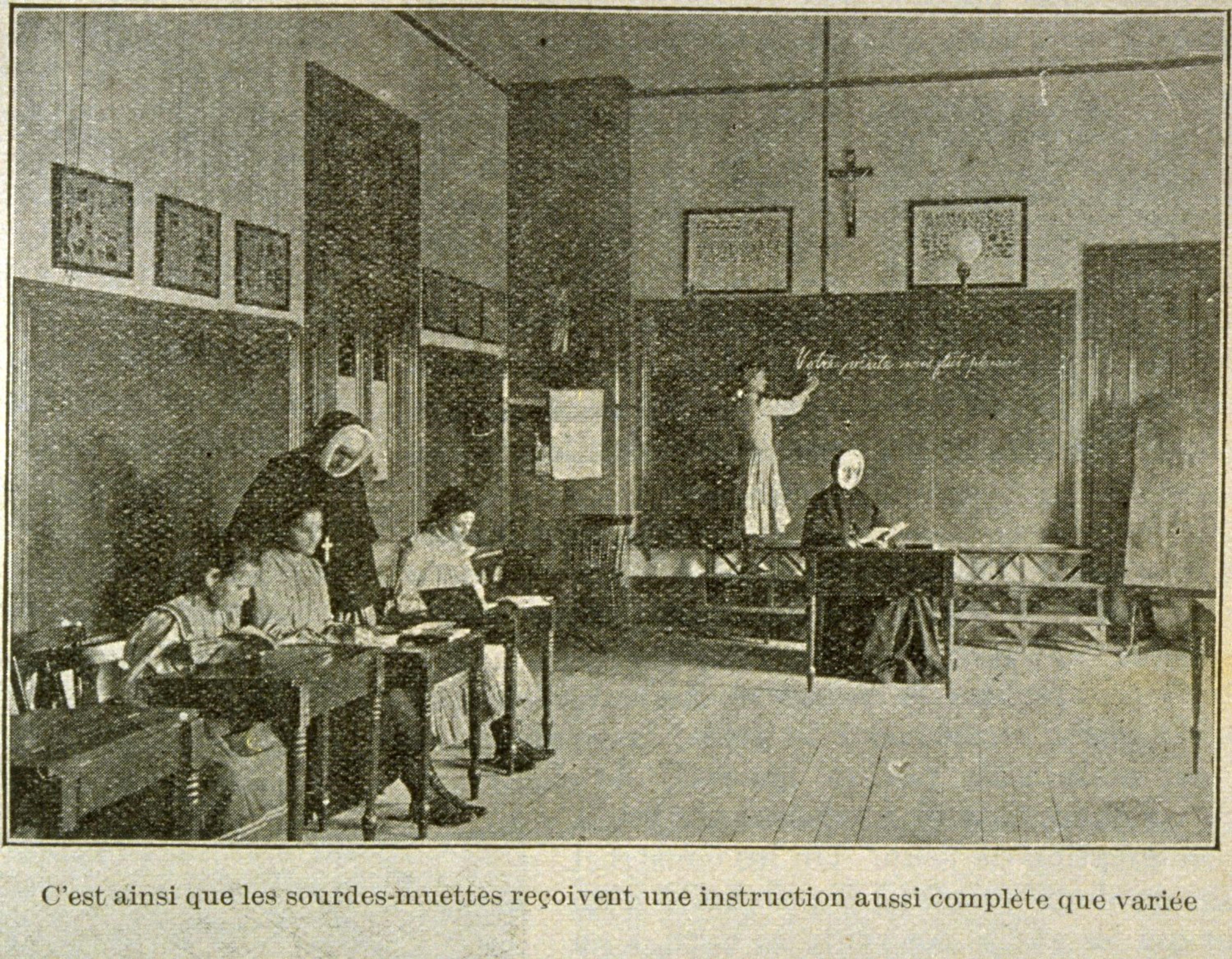 Vieille photo en noir et blanc montrant une salle de classe avec deux religieuses et quatre jeunes filles.