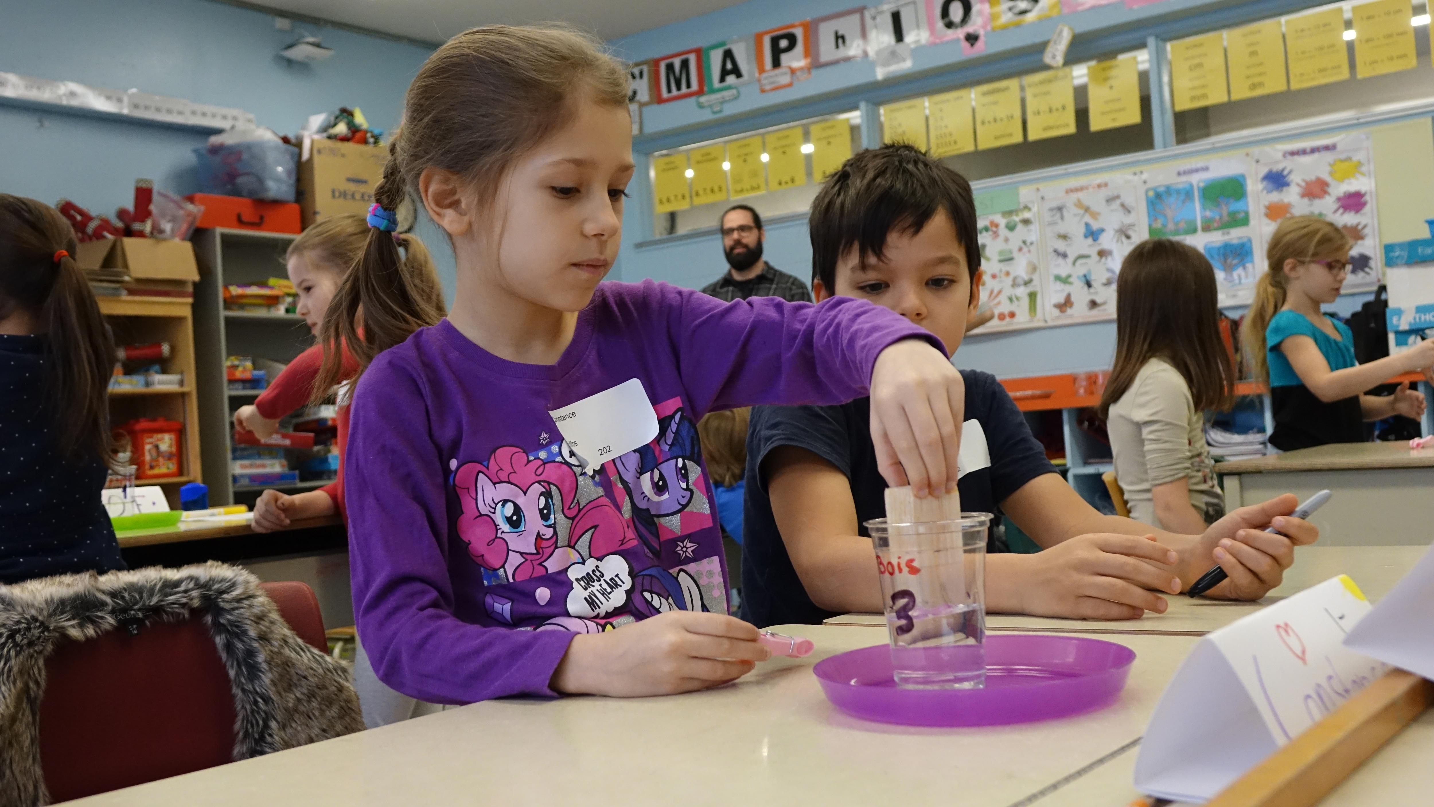 Une jeune élève qui fait une expérience scientifique