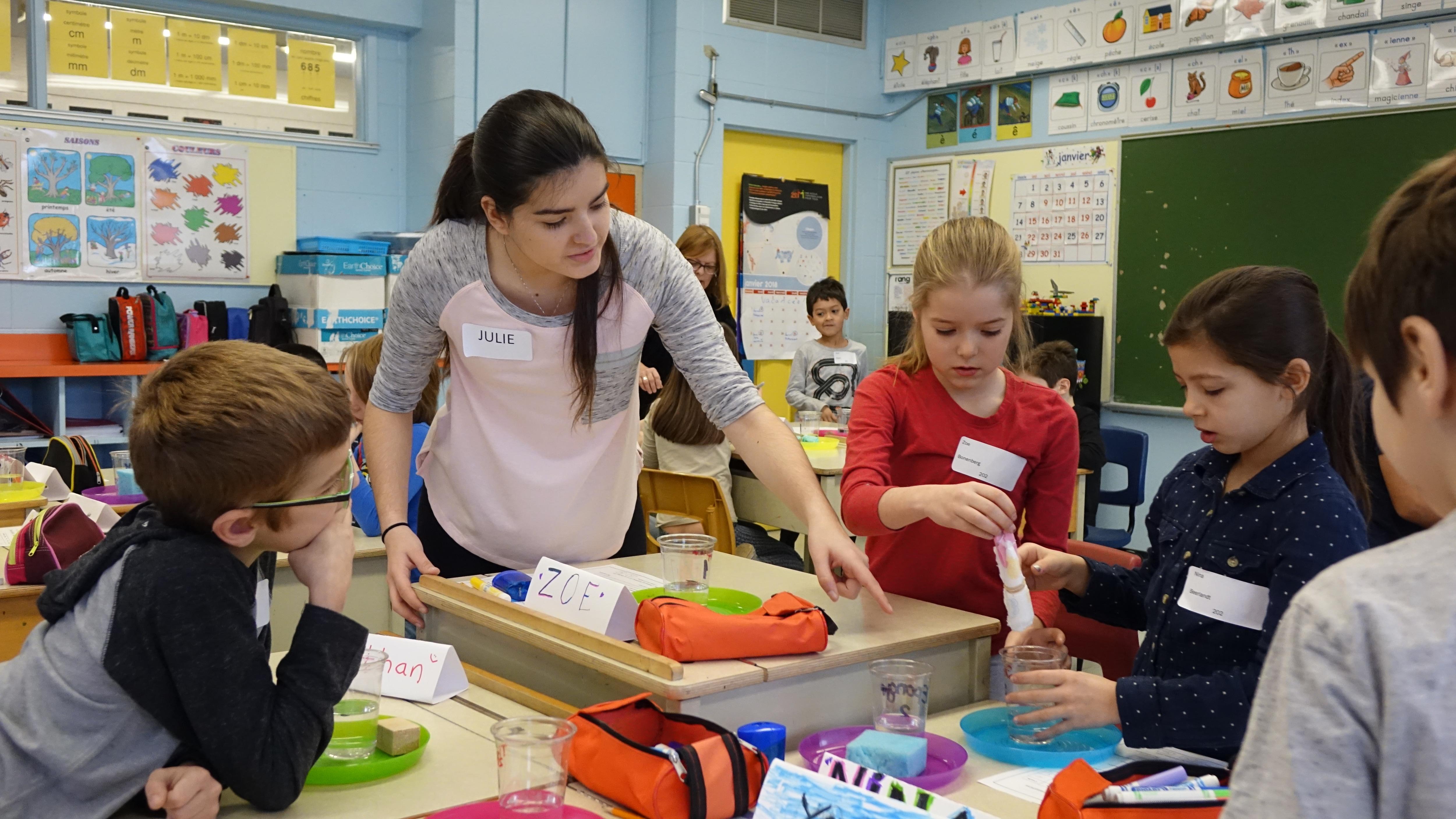 L'étudiante en arts et sciences au Cégep de Saint-Laurent Julie Morin-Genest guide les enfants, qui font leur expérience sur leurs bureaux.