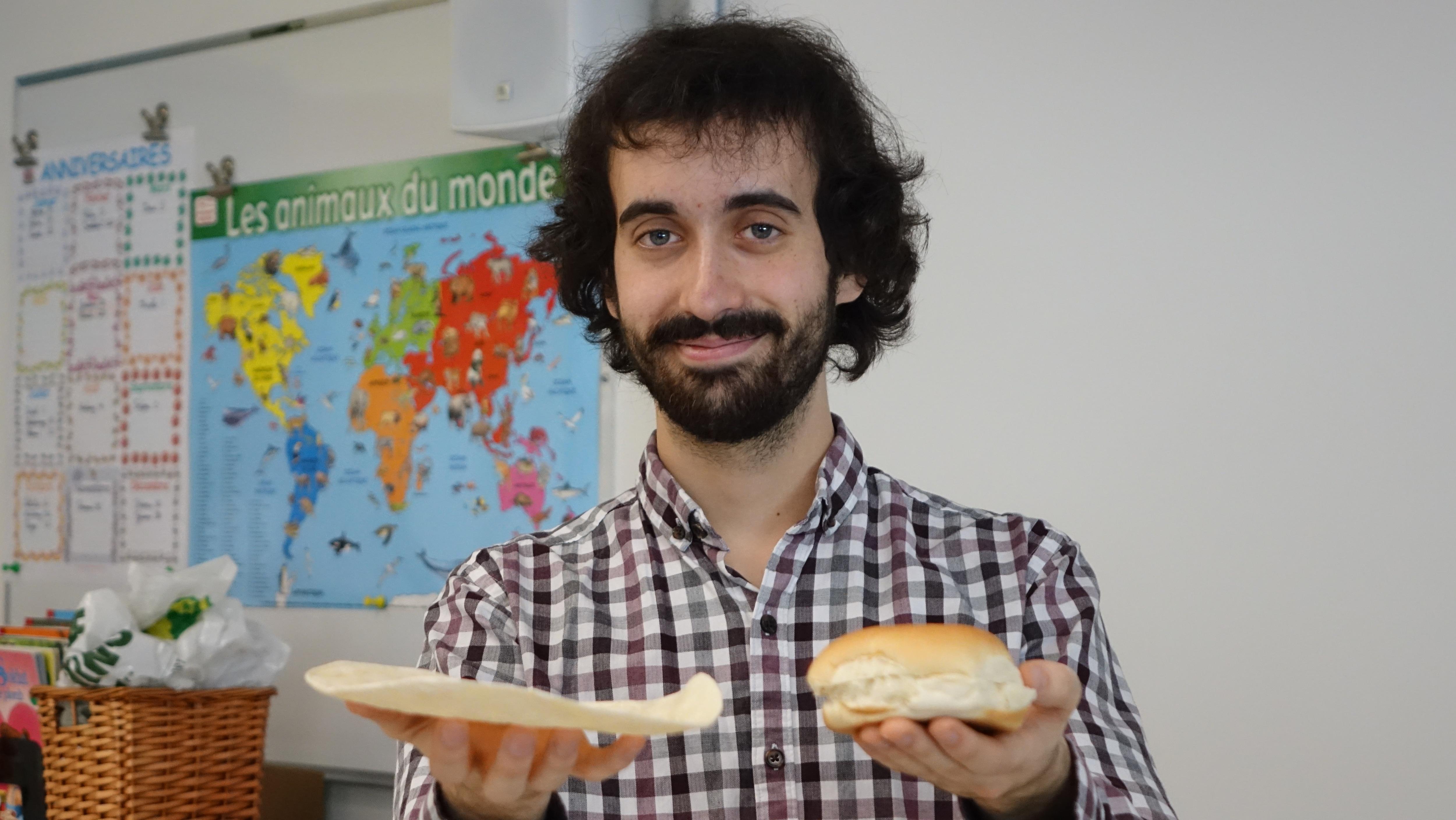 Un homme tient deux pains, un pain pita et un pain à hamburger, dans ses mains.