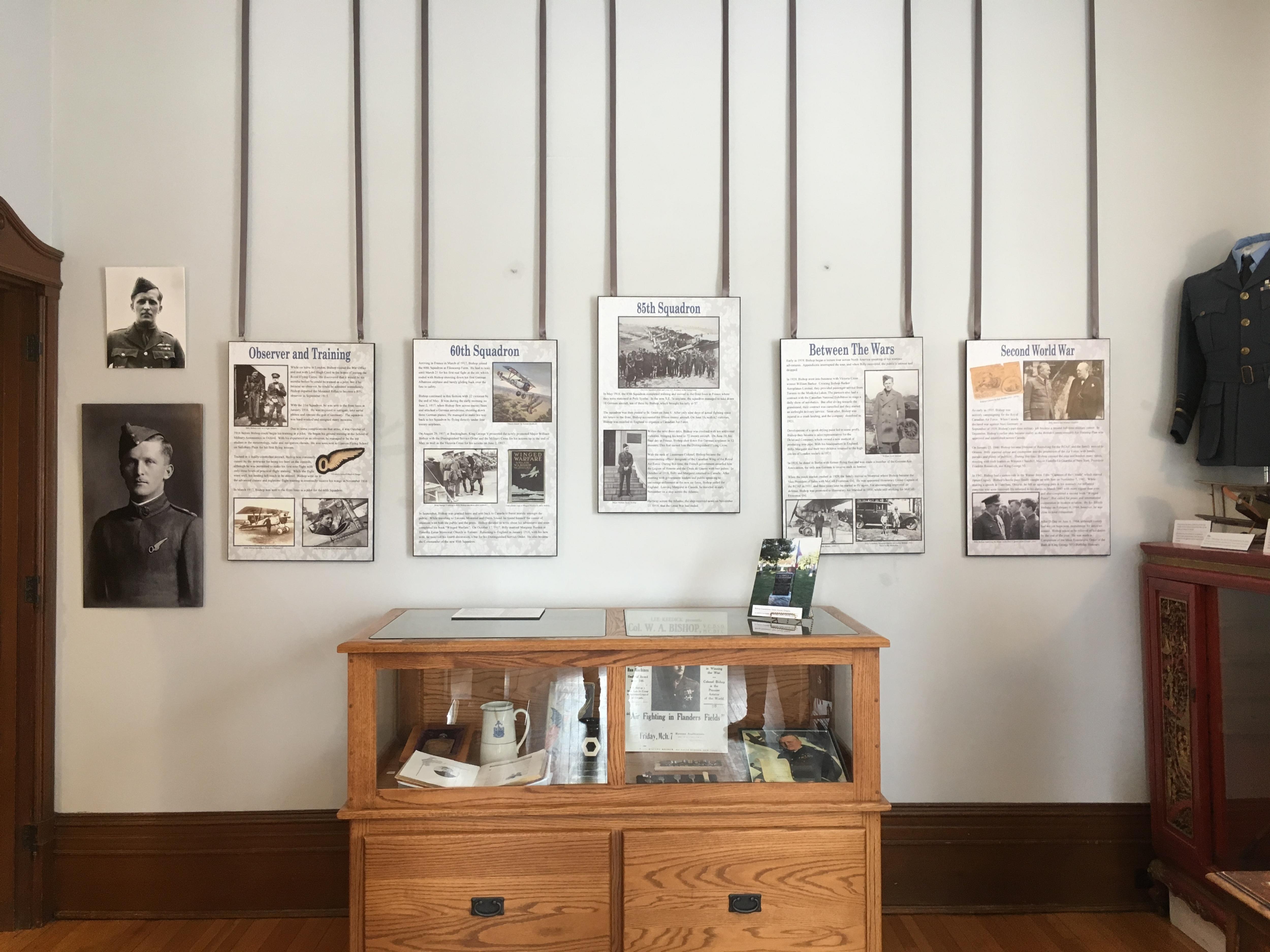 Les panneaux sont accrochés au mur au dessus d'un meuble vitrine