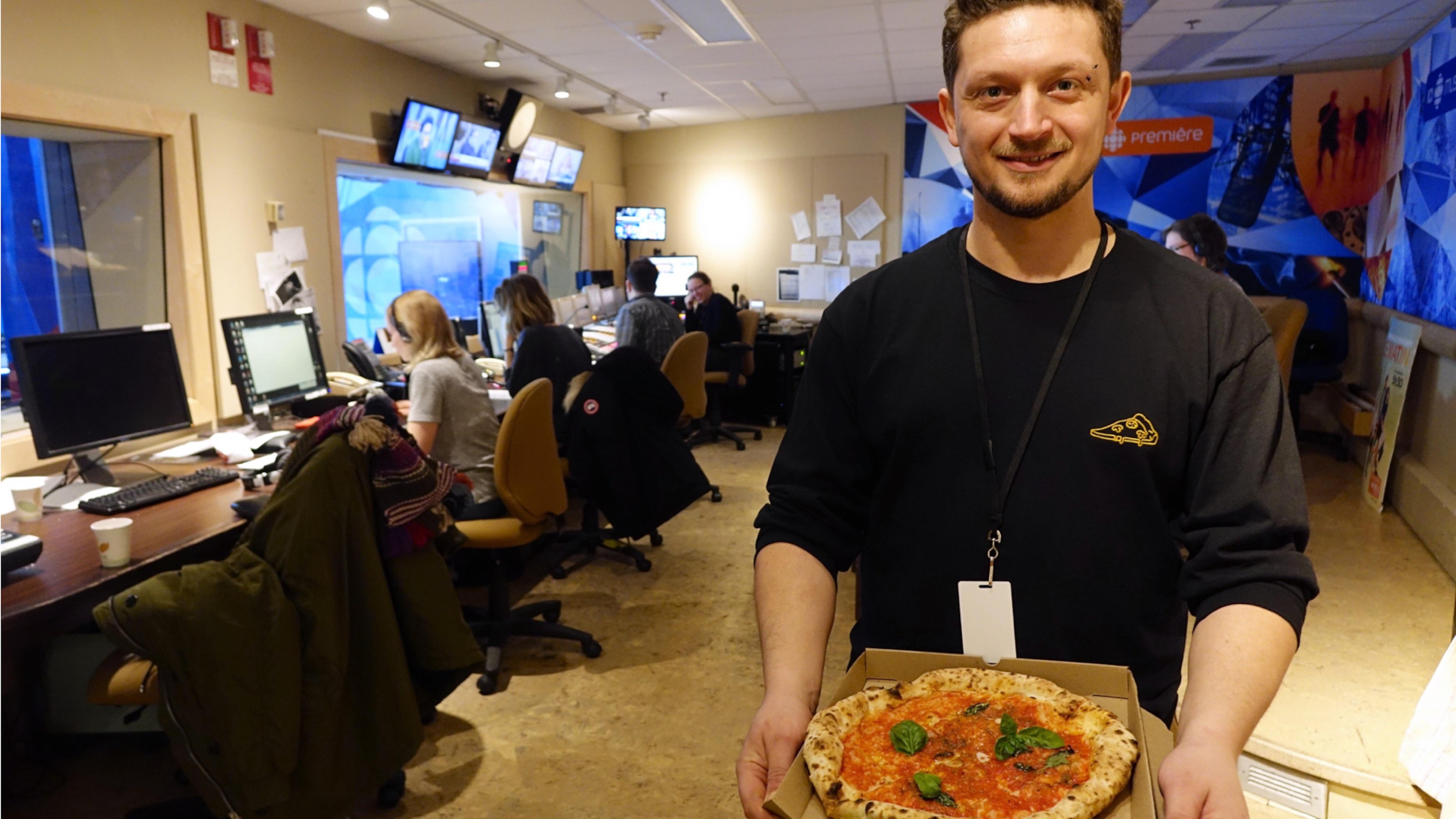 Mirko D'Agata tenant une pizza dans un studio de Radio-Canada