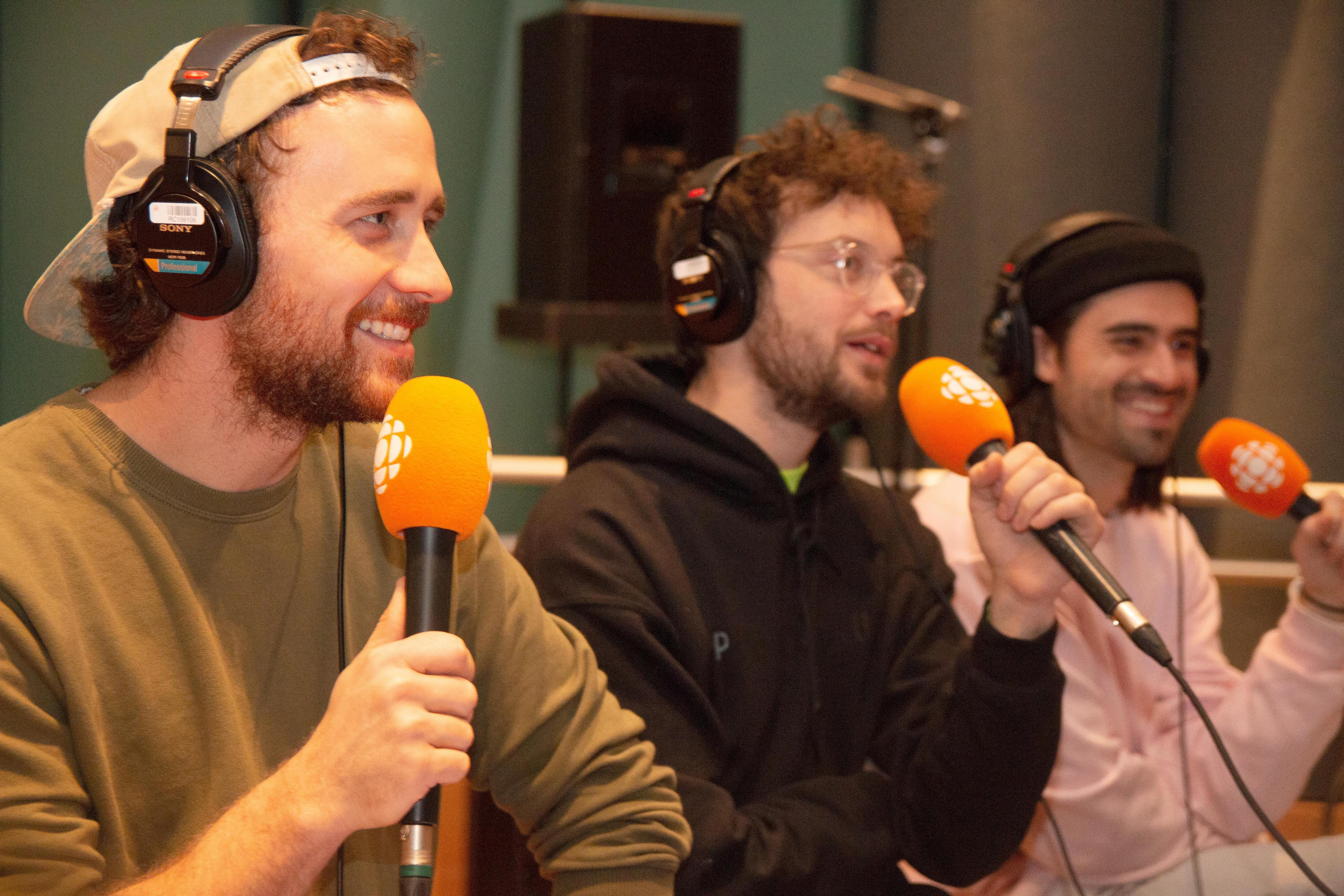 Trois hommes alignés tiennent chacun un micro dans leur main.