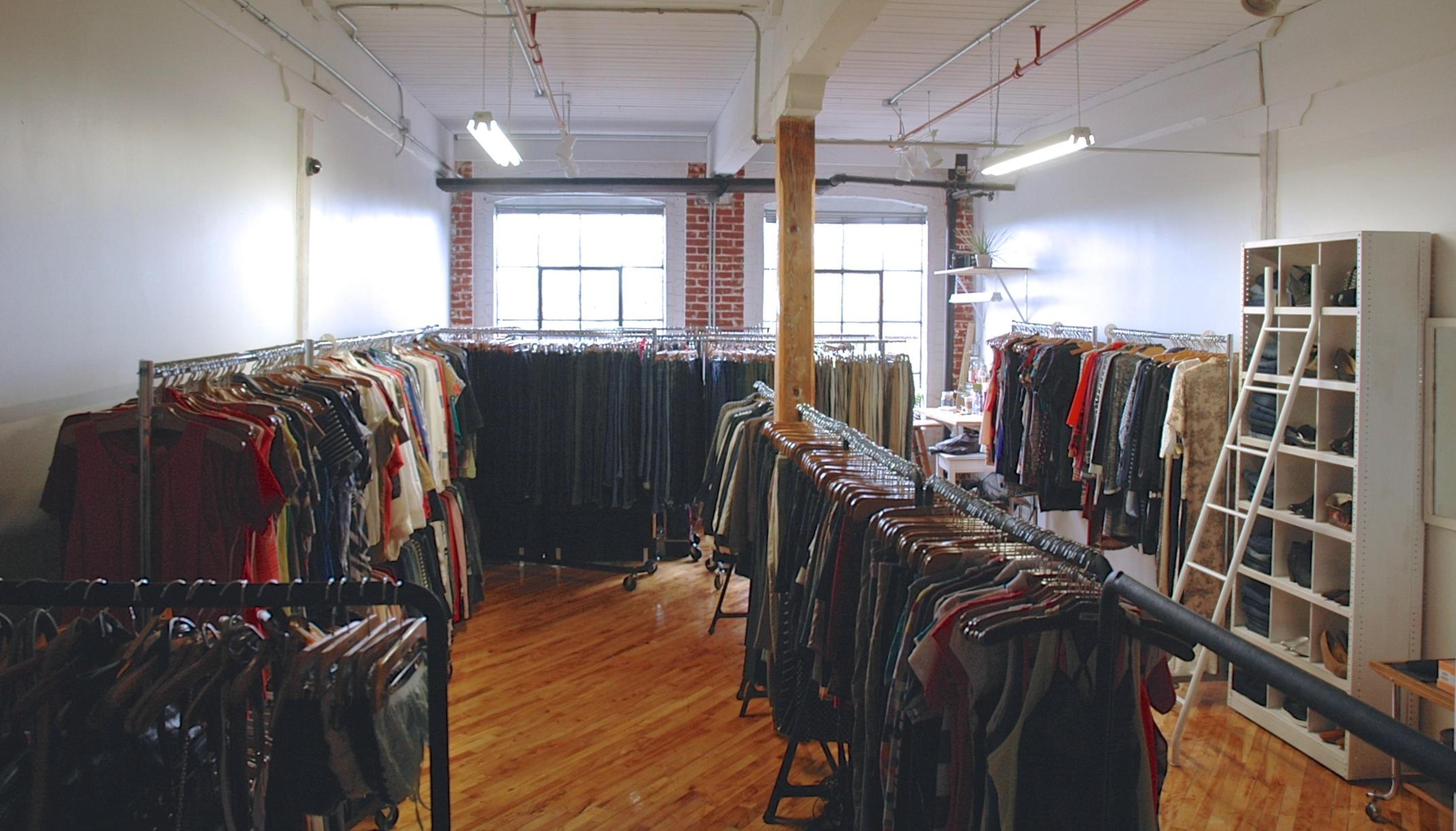 Un salle remplie de vêtements suspendus sur des cintres.