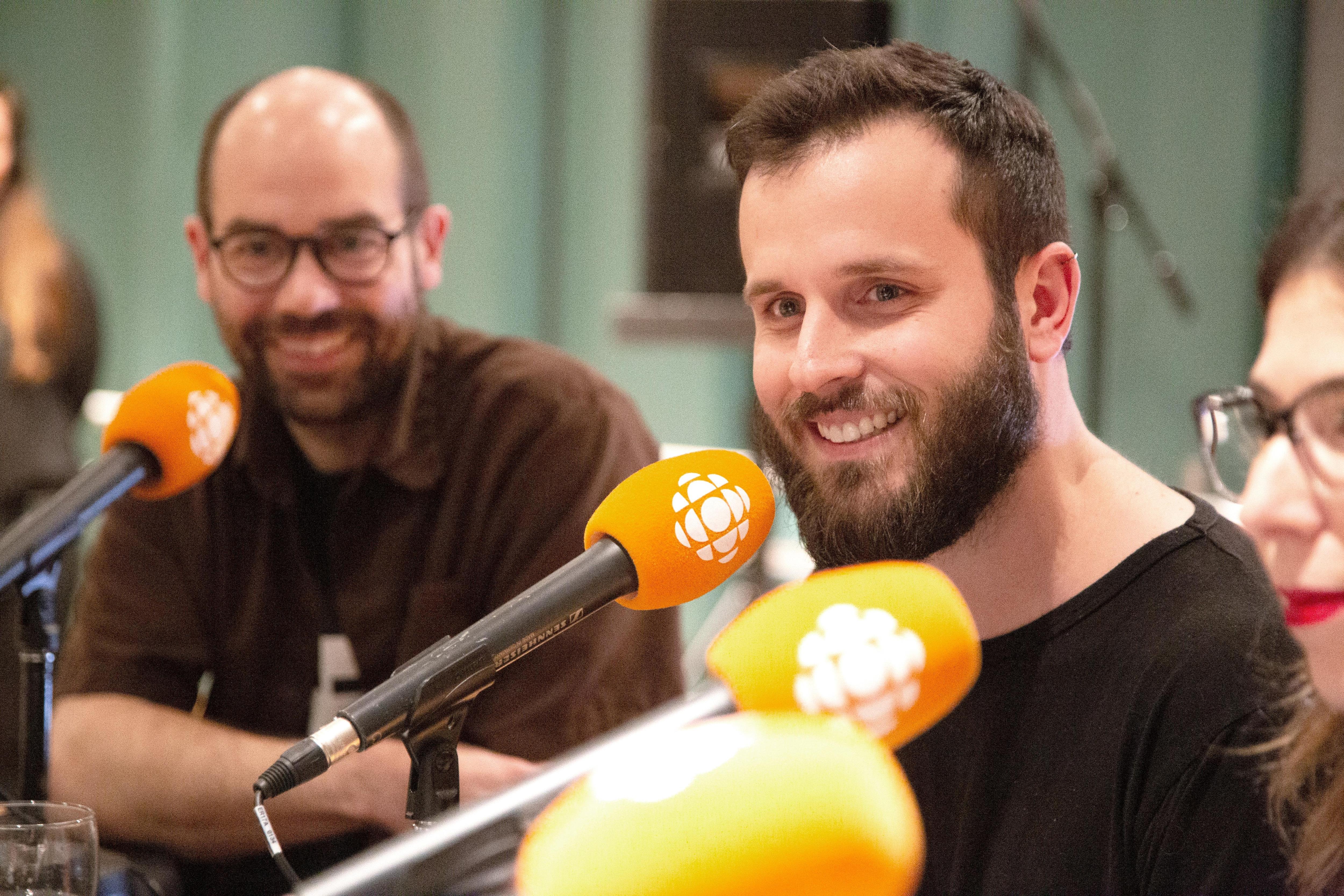 Assis derrière un micro, les deux hommes barbus sourient.