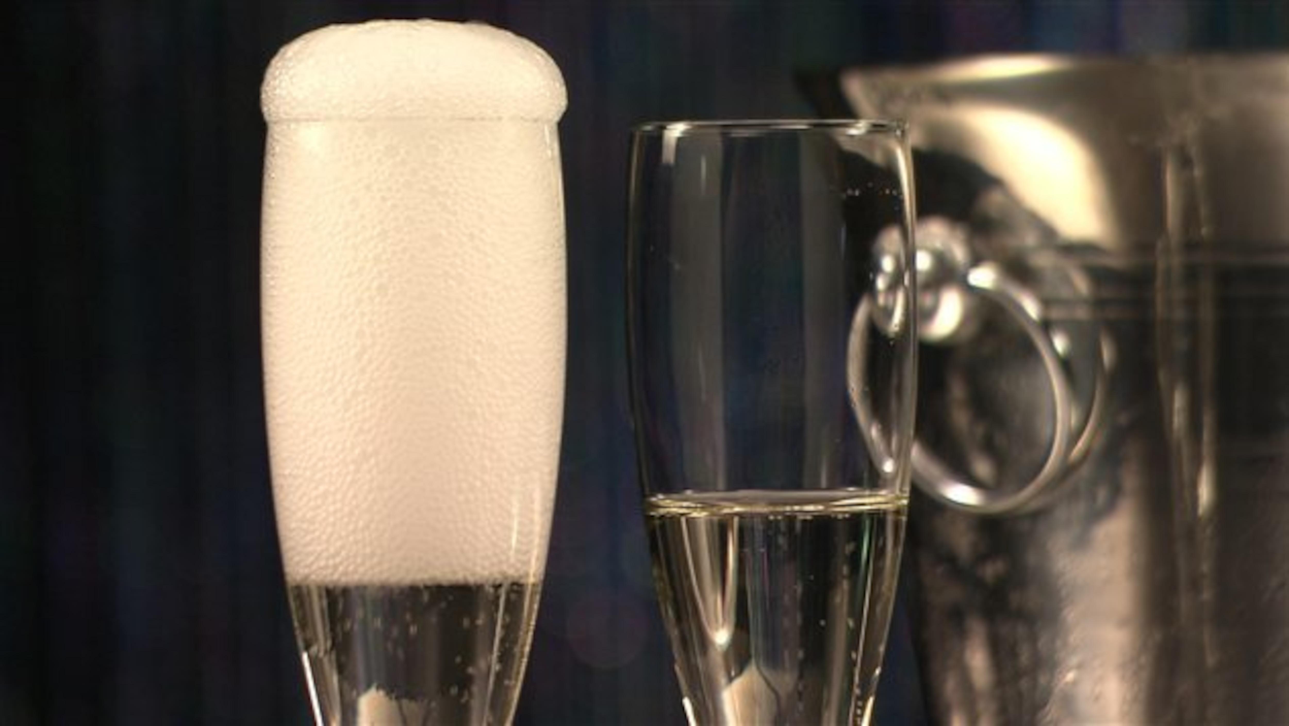 Deux flûtes de champagne devant un seau à glace.