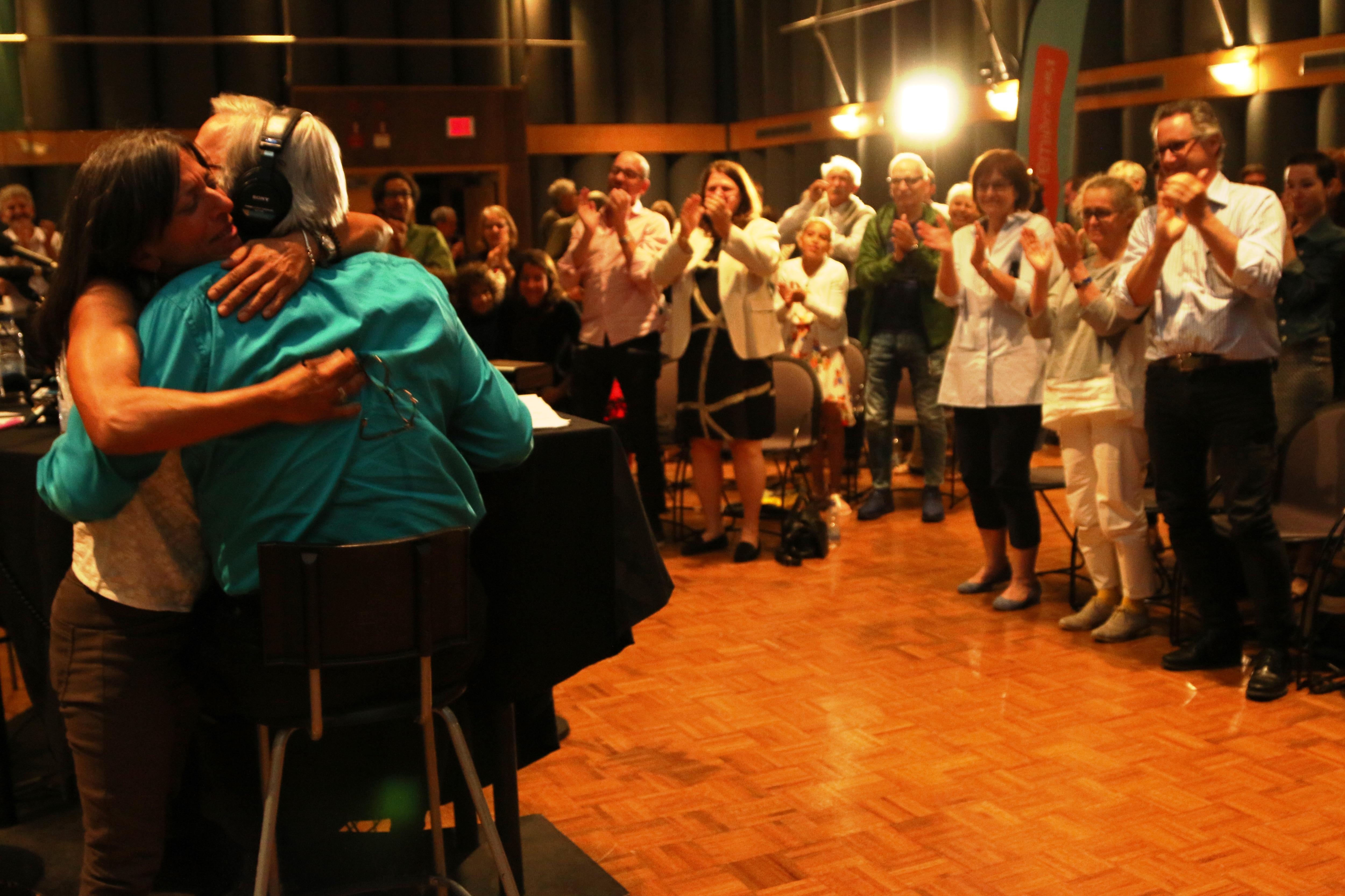 Émue, la journaliste Chantal Srivastava serre Yanick Villedieu dans ses bras pendant qu'amis, collègues et ex-collègues applaudissent l'animateur des Années lumière.
