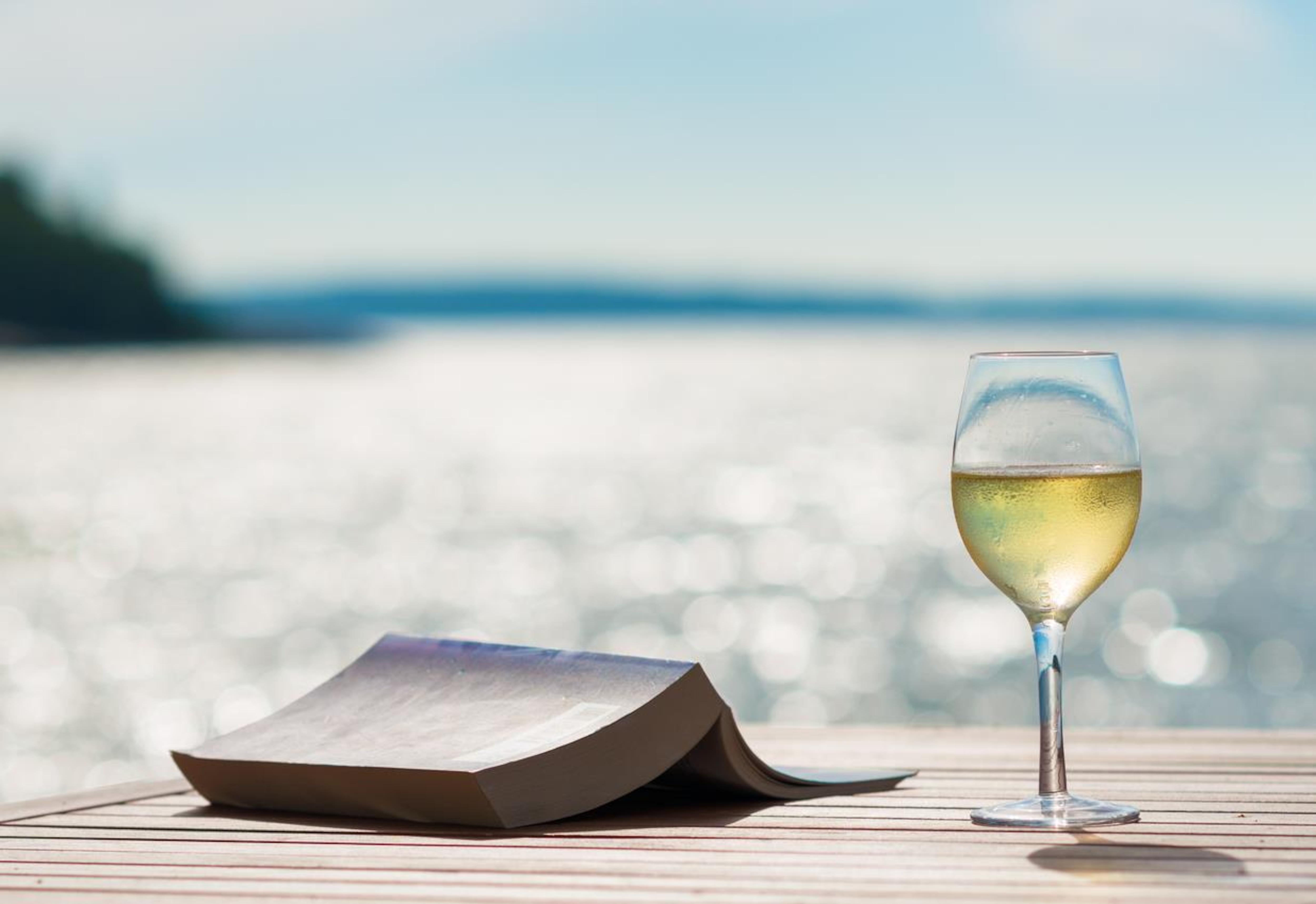 Un livre et un verre de vin blanc sont posés sur une table à l'extérieur