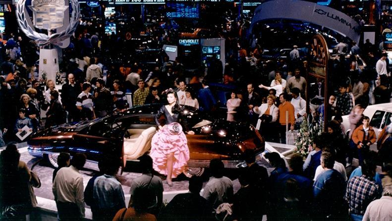 Des douzaines de personnes entourent une personne qui présente une automobile en 1989. Le décor autour ressemble à celui dans un casino, avec des lumières, des logos et une ambiance tamisée.